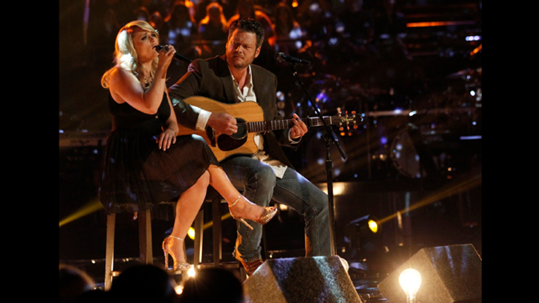 """This May 21, 2013 photo released by NBC shows married singers Miranda Lambert, left, and  Blake Shelton performing an acoustic version of the hit """"Over You"""" during a broadcast of the singing competition series, """"The Voice,"""" in Los Angeles."""