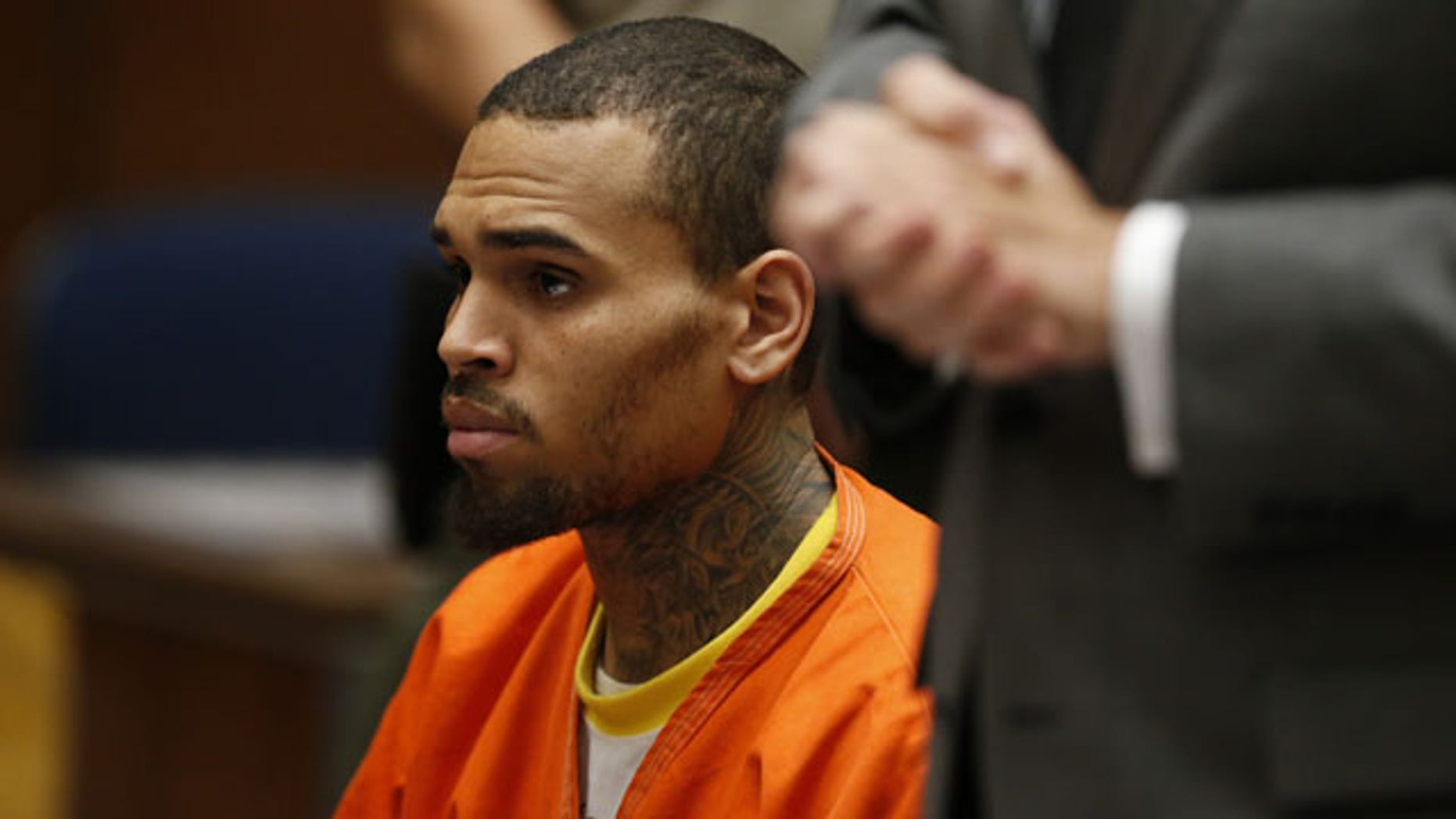 March 17, 2014: R&B singer Chris Brown, center, appears in Los Angeles Superior Court with his attorney Mark Geragos, right. Brown will spend another month in jail after a judge said Monday he was told the singer made troubling comments in rehab about being good at using guns and knives. (AP Photo/Lucy Nicholson, Pool)