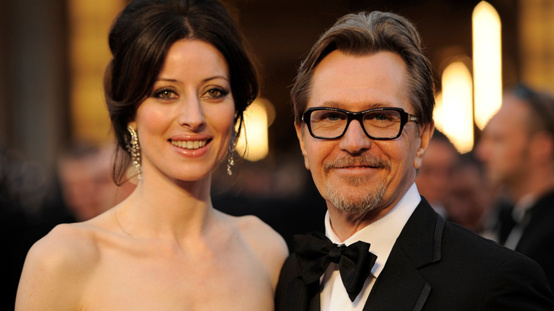 In this Feb. 26, 2012 file photo, Gary Oldman, right, and Alexandra Edenborough arrive before the 84th Academy Awards in the Hollywood section of Los Angeles.