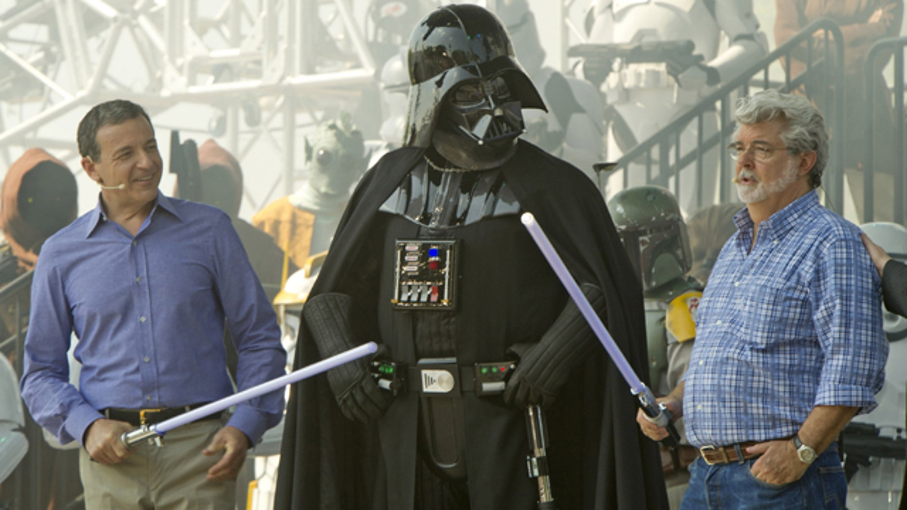 """In this publicity image released by Disney, Walt Disney Co. president and CEO Bob Iger, left, and """"Star Wars"""" creator George Lucas, right, flank """"Star Wars"""" character Darth Vadar during grand opening ceremonies for Star Tours - The Adventures Continue, a new 3-D attraction based on the films  in Disney's Hollywood Studios theme park in Lake Buena Vista, Fla., Friday, May 20, 2011.   (AP Photo/Disney, Kent Phillips)"""