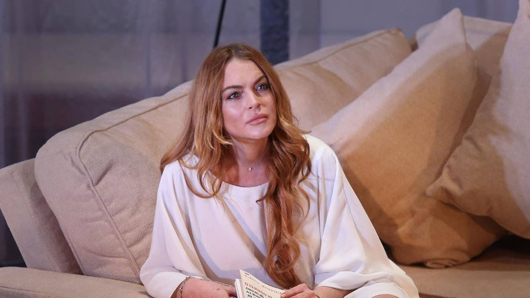 """FILE - In this Tuesday, Sept. 30, 2014 file photo, U.S actress Lindsay Lohan performs a scene from the play, """"Speed the Plow,"""" during a photocall at the Playhouse Theatre in central London. Lohan's wreckless driving case is scheduled to be called in a Los Angeles court on Thursday, May 7, 2015, to update the judge on her progress with community service. (Photo by Joel Ryan/Invision/AP, File)"""