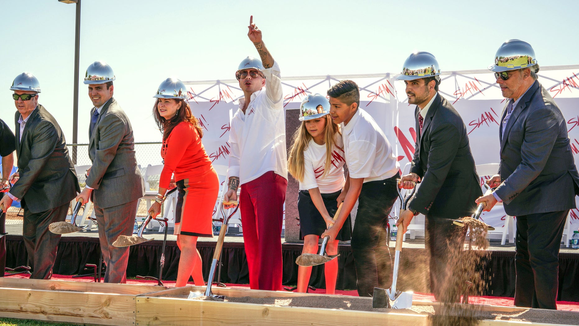 In this photo provided by Pitbull, Rapper Pitbull, fourth from left, gestures during a groundbreaking ceremony for SLAM!,  the school whose name stands for Sports Leadership and Management Academy, on Friday, Oct. 2, 2015, in Henderson, Nev. The school that ties sports themes to its curriculum for students seeking careers in sports medicine, marketing, business and management is expected to open in time for the 2016 school year for students in grades six through nine. Pitbull opened his first SLAM! School in Miami in 2013. (Greg Watermann for Pitbull  via AP )