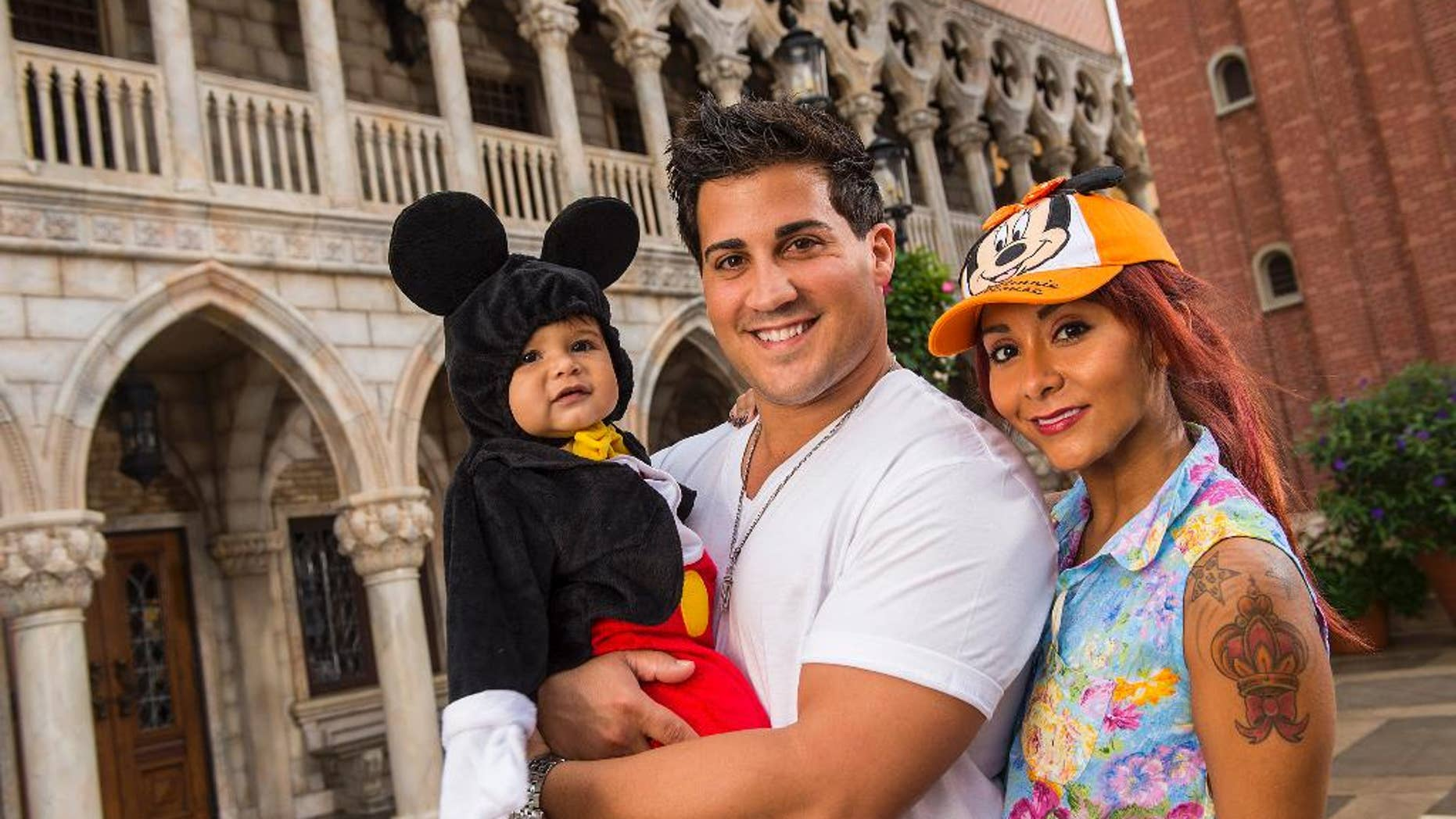 """FILE - This image released by Disney shows TV personality Nicole """"Snooki"""" Polizzi, right, from """"Jersey Shore,"""" with her fiance Jionni LaValle and their one-year-old son Lorenzo inside the Italy pavilion in the Epcot theme park, in this Sept. 27, 2013 file photo taken  at Walt Disney World in Lake Buena Vista, Fla. The cast member of the reality series """"Jersey Shore"""" and """"Snooki and JWoww"""" spinoff intends to marry her fiance Jionni LaValle at the Venetian banquet hall in Garfield in the fall 2014. (AP Photo/Disney, Matt Stroshane, File)"""