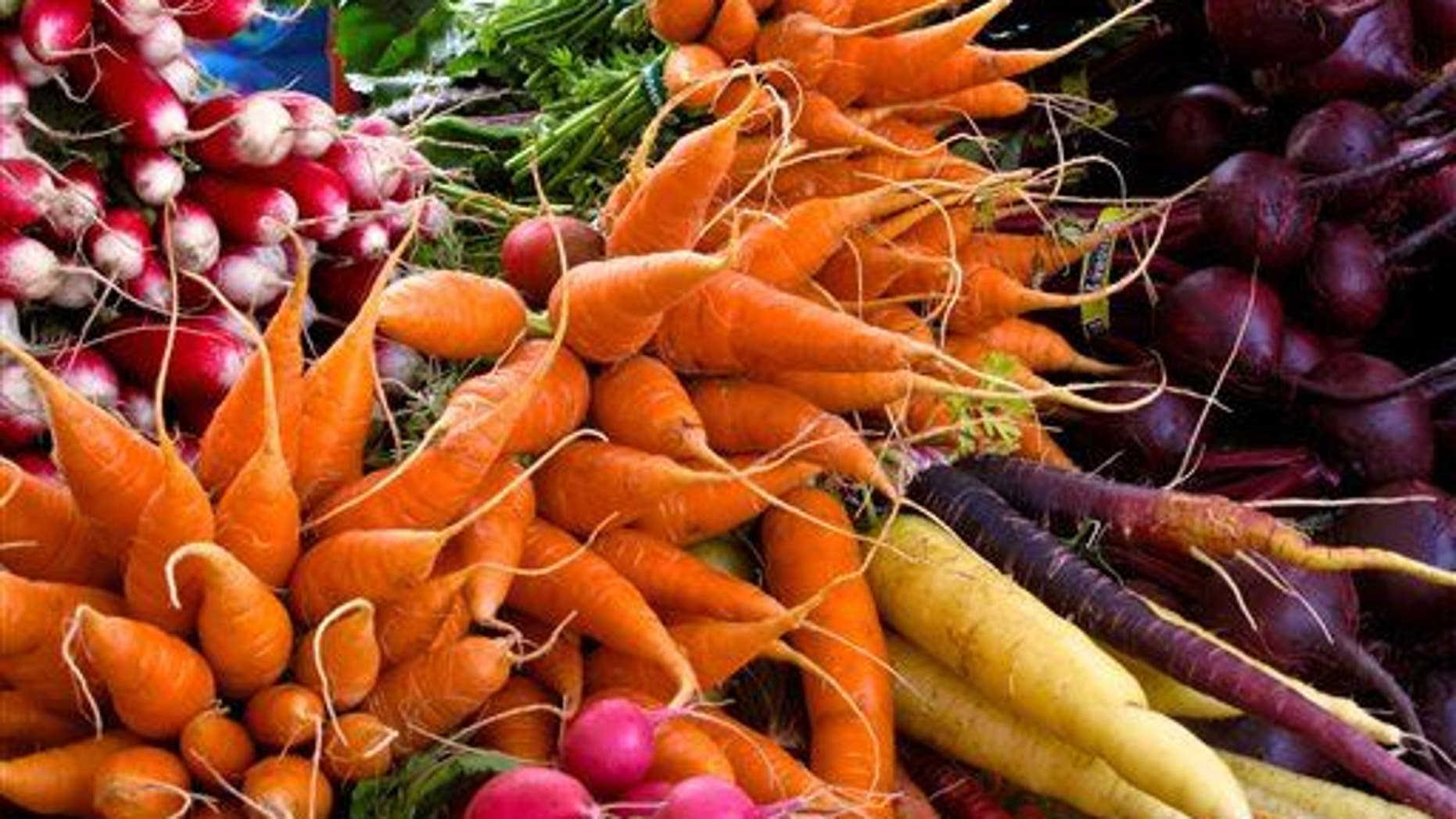 This photo taken on Oct. 5, 2013, shows radishes, carrots, turnips, and beets at a farmers market near Langley, Wash.