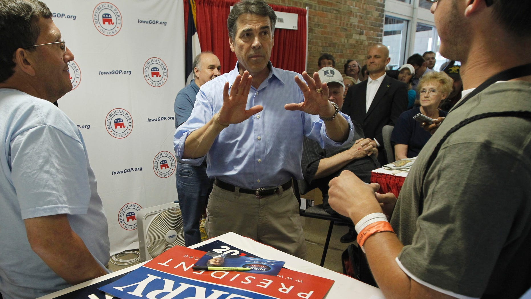 August 15: Flyers for Rep. Michele Bachmann, R-Minn. and former Alaska Gov. Sarah Palin can be seen on the table as Republican presidential candidate, Texas Gov. Rick Perry visits the Iowa GOP Booth at the Iowa State Fair in Des Moines.