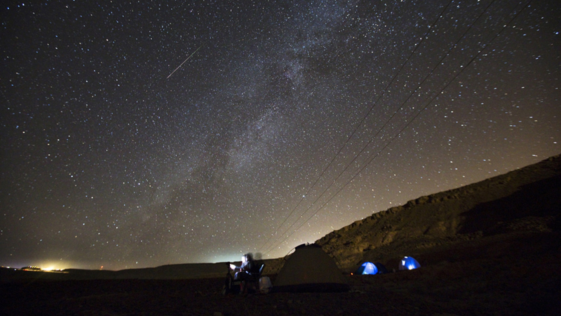 File photo - a meteor streaks across the sky in the early morning as people watching during the Perseid meteor shower in Ramon Carter near the town of Mitzpe Ramon, southern Israel, Aug.13, 2015.