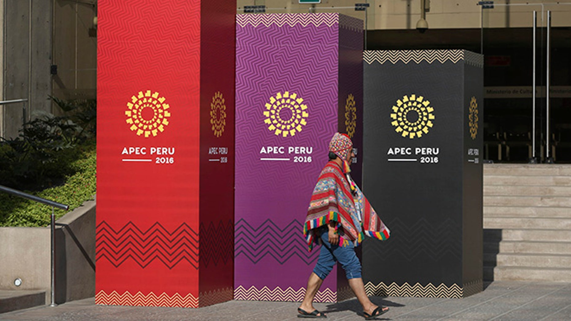 A man dressed in traditional Andean clothes walks past the logo of the APEC 2016 summit in Lima, Peru.