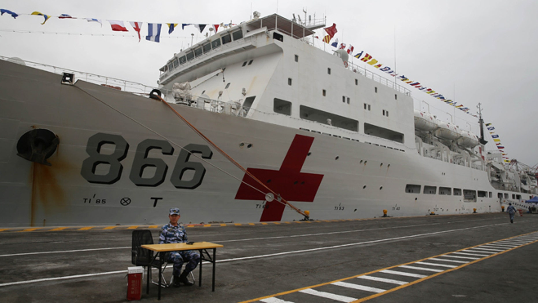 A Chinese official sits in front of Chinese naval hospital ship in the port of Callao, Peru, Tuesday, Dec. 22, 2015. The Peace Ark, a Chinese naval hospital ship is making a first-ever call into a South American port in a sign of the Asian economic giants growing influence in Washingtons backyard. Its the last destination on a three-month Harmonious Mission that also included stops in Australia, Mexico and the U.S. (AP Photo/Martin Mejia)