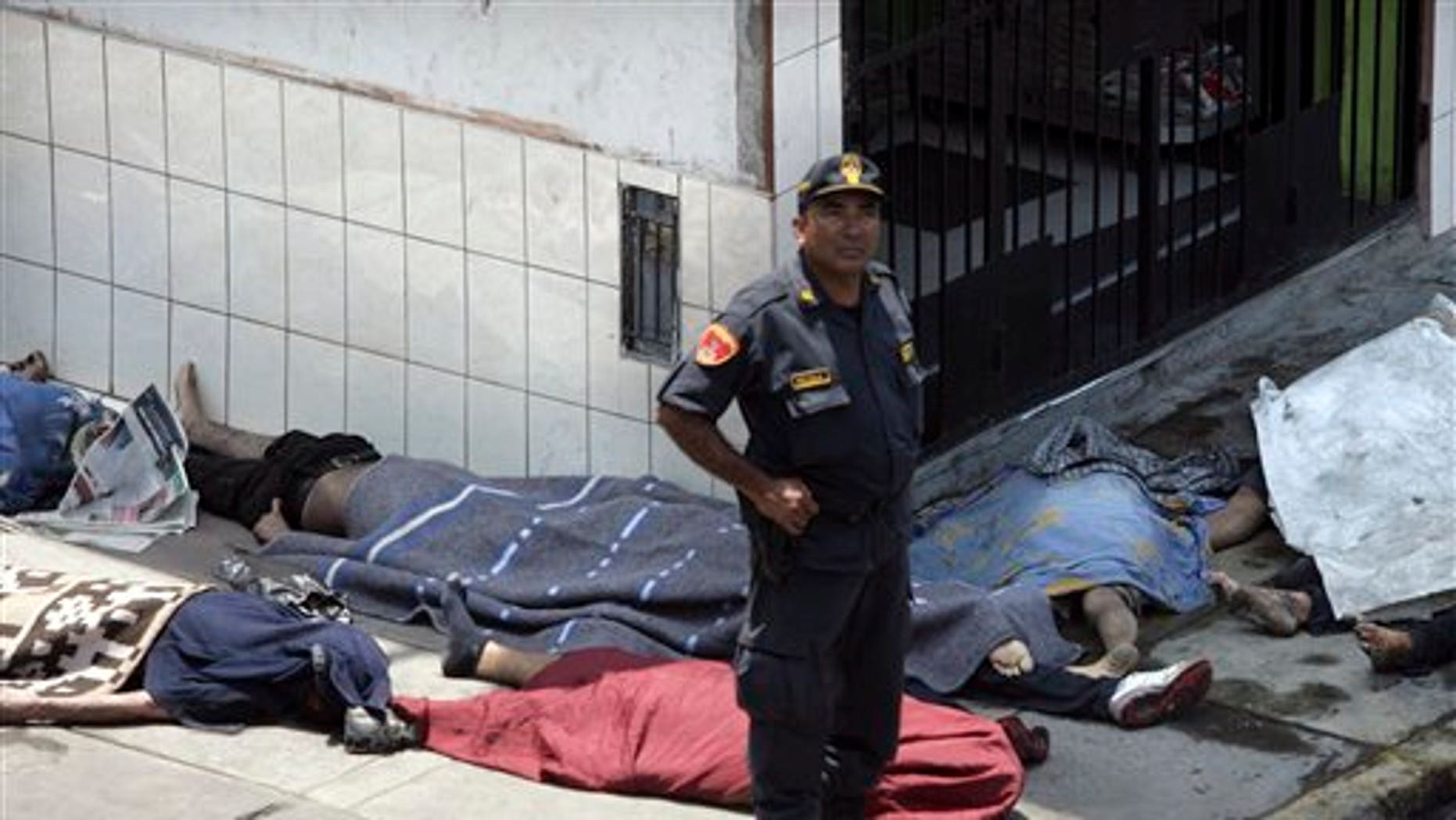 Jan. 28: A police officer stands next to a group of bodies outside the 'Christ is Love' center for drug and alcohol addicts in Lima, Peru.