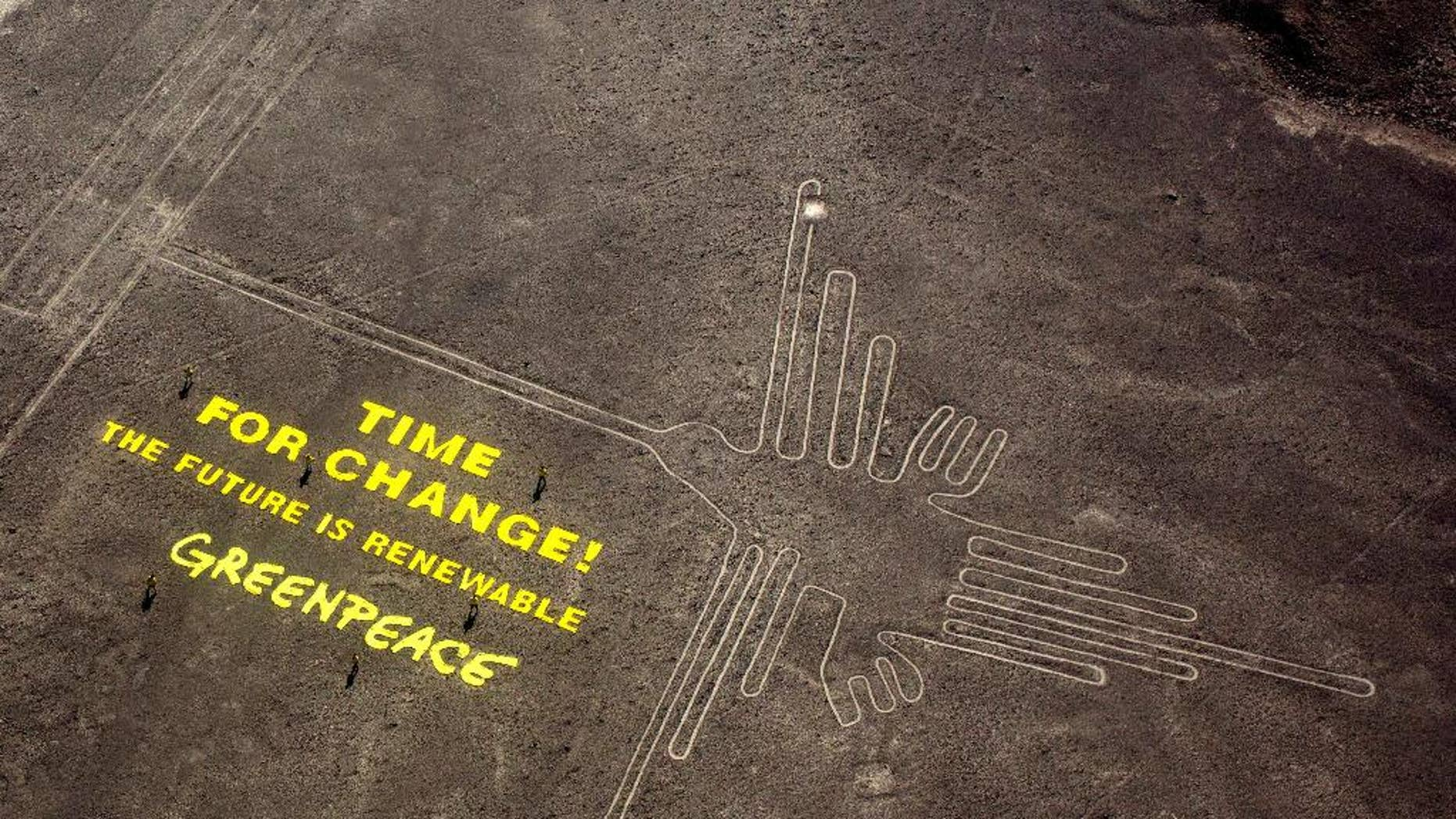 """FILE - In this Dec. 8, 2014 file photo, Greenpeace activists stand next to large letters that spell out """"Time for Change: The Future is Renewable"""" next to the hummingbird geoglyph in Nazca, Peru. A Peruvian prosecutor is investigating the suspected involvement of Greenpeace activist Mauro Fernandez in the publicity stunt that allegedly damaged the world-renowned Nazca lines that date to some 1,500 to 2,000 years ago. Authorities have said the fragile site was damaged by footprints. (AP Photo/Rodrigo Abd, File)"""