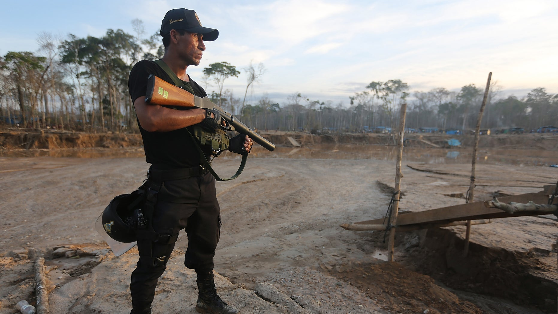MADRE DE DIOS REGION, PERU - NOVEMBER 17:  A National Police officer searches an illegal mining operation in the Amazon lowlands on November 17, 2013 in Madre de Dios region, Peru. Police eventually destroyed three pieces of illegal mining equipment in the area. The biologically diverse Madre de Dios ('Mother of God') region has seen deforestation from gold mining in the area triple since 2008, when gold prices spiked during global economic turmoil. Small-scale miners are drawn to the area in hopes for higher pay but often face abysmal conditions. Gold is usually amalgamated with mercury during the process of informal mining in the region, which is discharged into the water supply and air, poisoning fish and sickening people in the area. Peru is the largest producer of gold in Latin America and the sixth-largest in the world. Informal mining accounts for roughly 20 percent of the gold production in Peru.  (Photo by Mario Tama/Getty Images)