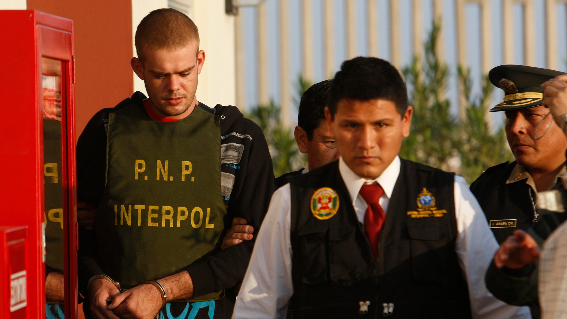 Peru's police officers escort Dutch citizen Joran Van der Sloot, left, outside a Peruvian police station, near the border with Chile in Tacna, Peru, Friday, June 4, 2010. The suspect is accused of stabbing three fellow inmates in a Peruvian prison. (AP)