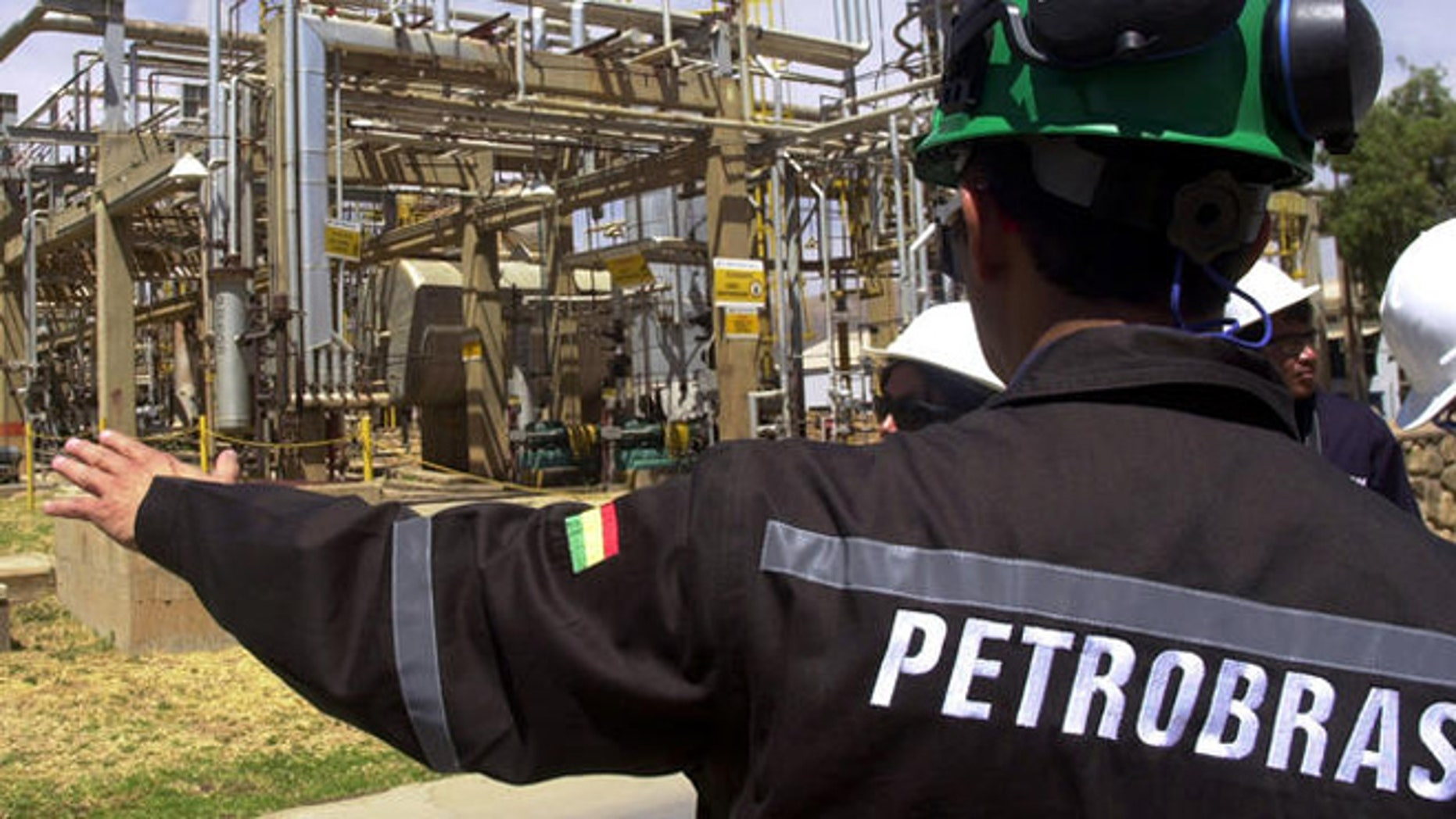 A Bolivian employee of Brazil's oil giant Petrobras subsidiary Petrobras Bolivia  shows a natural gas facility at the Gualberto Villarroel , 8m (about 5 miles) south of Cochabamba, Bolivia, Tuesday, Sept. 5, 2006. The nationalization of Bolivia's hydrocarbons industry took two steps forward this week as the government opened long-awaited contract negotiations with foreign petroleum companies while collecting the first round of higher royalties it now charges those firms. Representatives of the French company Total S.A. sat down with Hydrocarbons Ministry officials Tuesday in La Paz to begin drawing up a new contract ceding a majority share of their Bolivian operations to the government, as required by President Evo Morales' May 1 nationalization decree. Contract negotiations with other international firms _ including Brazil's state-owned Petrobras and the Spanish-Argentine firm Repsol YPF _ are expected to follow.(AP Photo/Nano Cartagena)