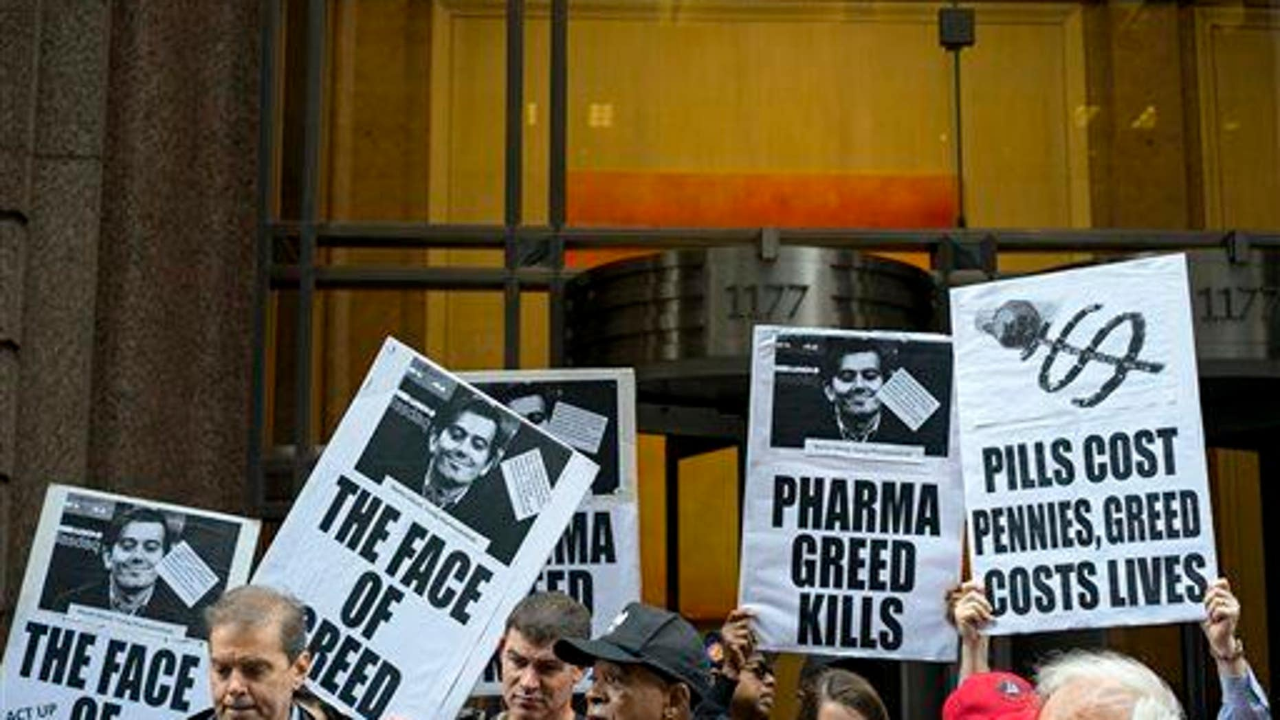 Activists hold signs containing the image of Turing Pharmaceuticals CEO Martin Shkreli in front of Turing's offices in New York on Oct. 1, 2015, during a protest.