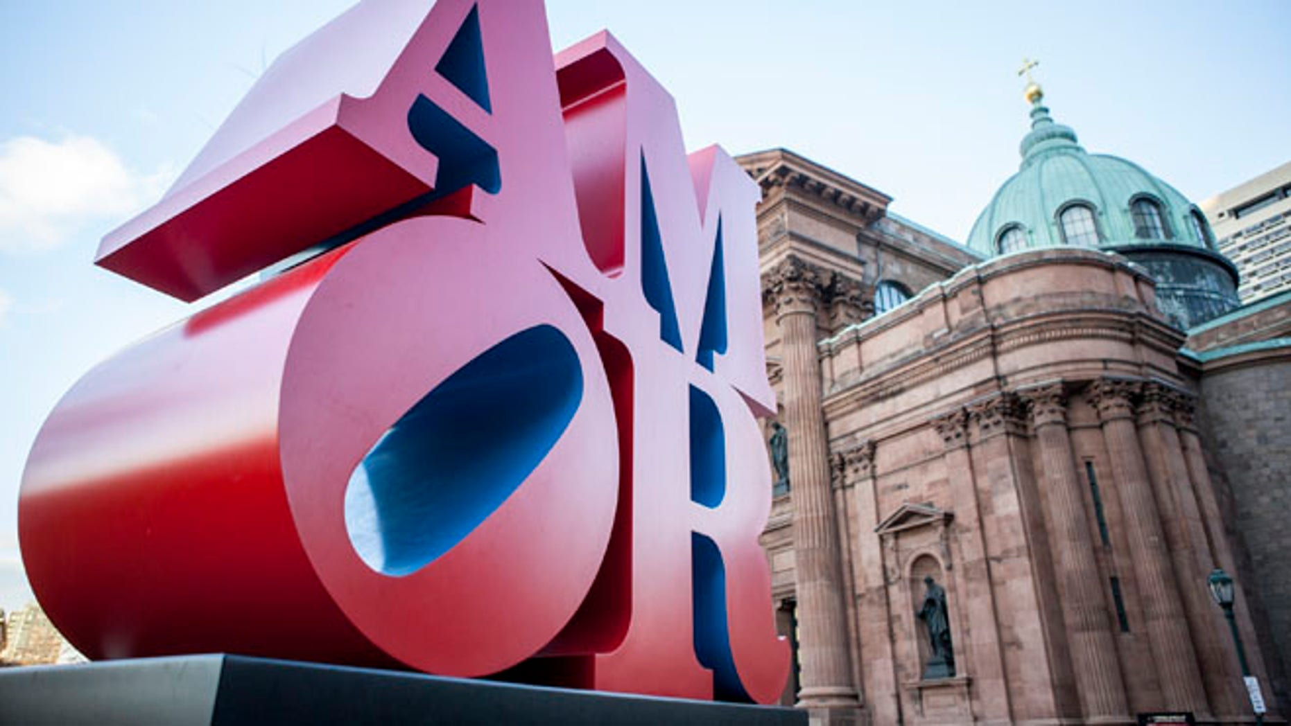 This photo shows Robert Indiana's AMOR sculpture in a park outside Philadelphia's Cathedral Basilica of Saints Peter and Paul, Friday, Dec. 2, 2016. Officials say the sculpture, originally loaned to Philadelphia for last year's papal visit, will permanently remain in the city. It's a Spanish and Latin version of Indiana's LOVE sculpture, which is a Philadelphia landmark. (AP Photo/Michael R. Sisak)