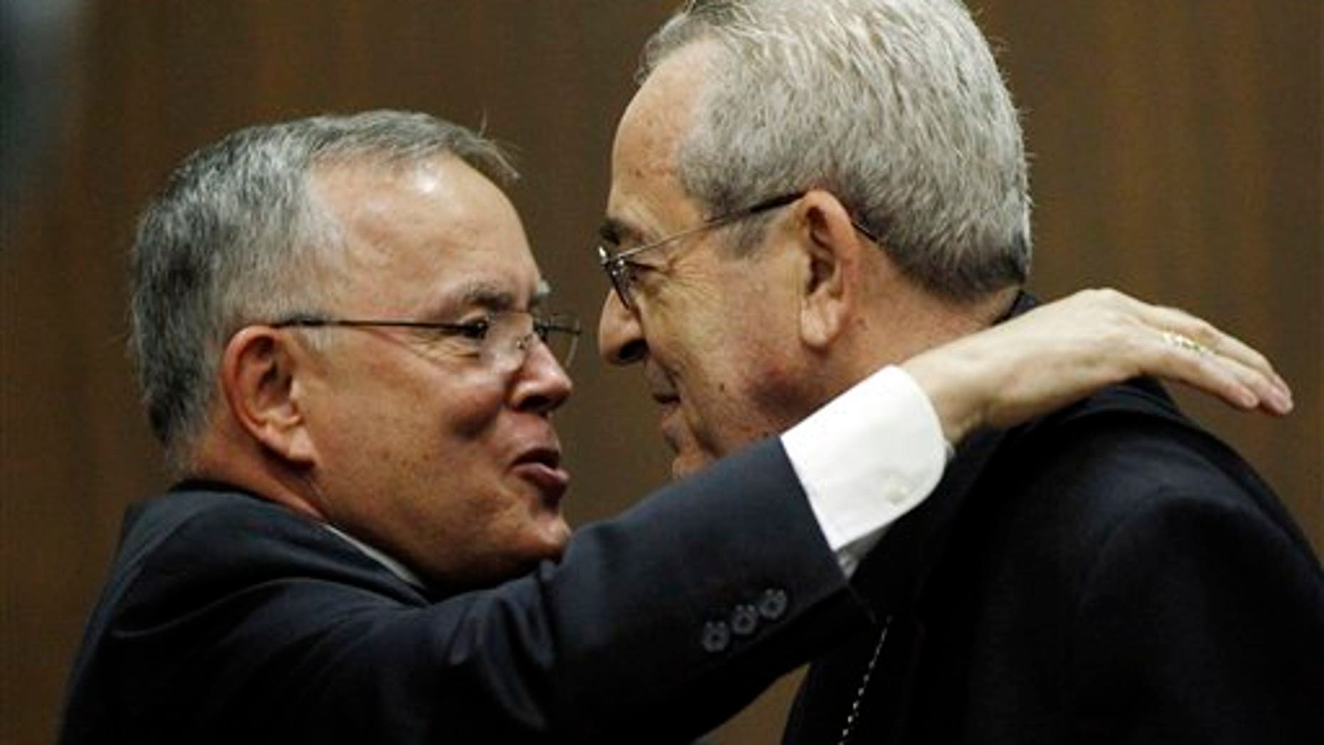 July 19: Denver Archbishop Charles Chaput, left, and Cardinal Justin Rigali embrace during a news conference in Philadelphia.