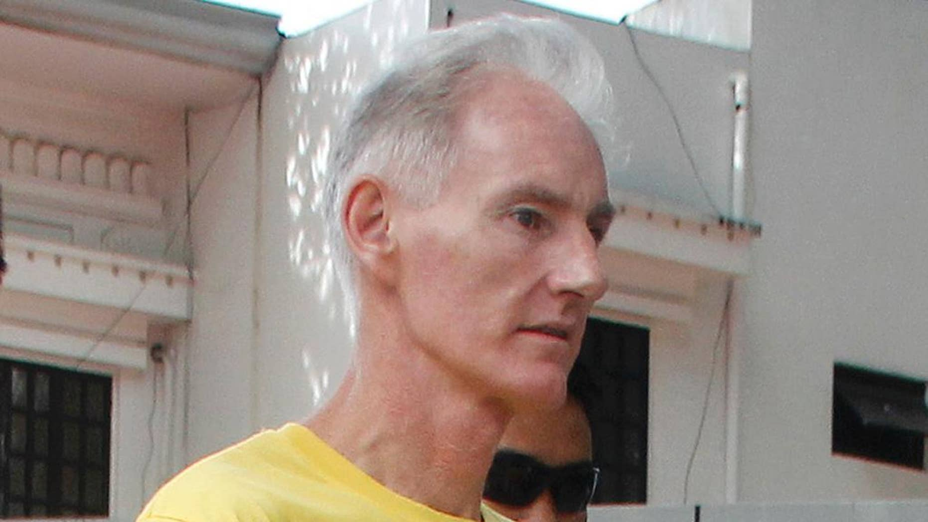 Peter Gerald Scully of Australia walks in handcuffs as he arrives at Cagayan de Oro city hall in southern Philippines on Tuesday, June 16, 2015. Scully and his Filipino girlfriend Carme Ann Alvarez have pleaded not guilty to charges of raping and trafficking two girls aged 9 and 12 in a southern Philippine city. (AP Photo)