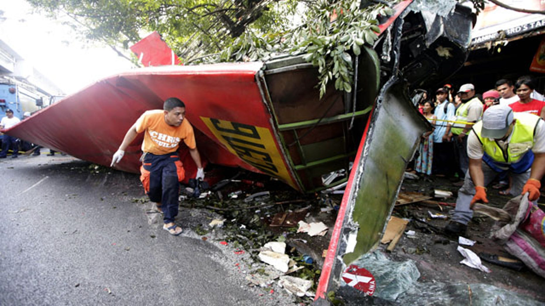 December 16, 2013: Investigators collect items from the wreckage of a passenger bus which plunged from an elevated highway known as the Skyway in suburban Paranaque southeast of Manila, Philippines.