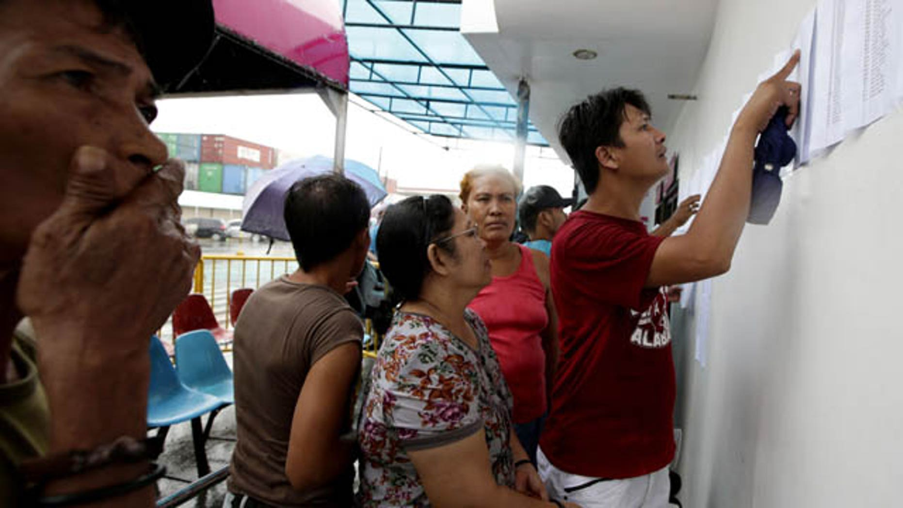 August 17, 2013: Relatives check the lists of survivors and the still-missing passengers and crew of the ill-fated passenger ferry MV Thomas Aquinas, outside the ticketing office of a shipping company. (AP Photo)