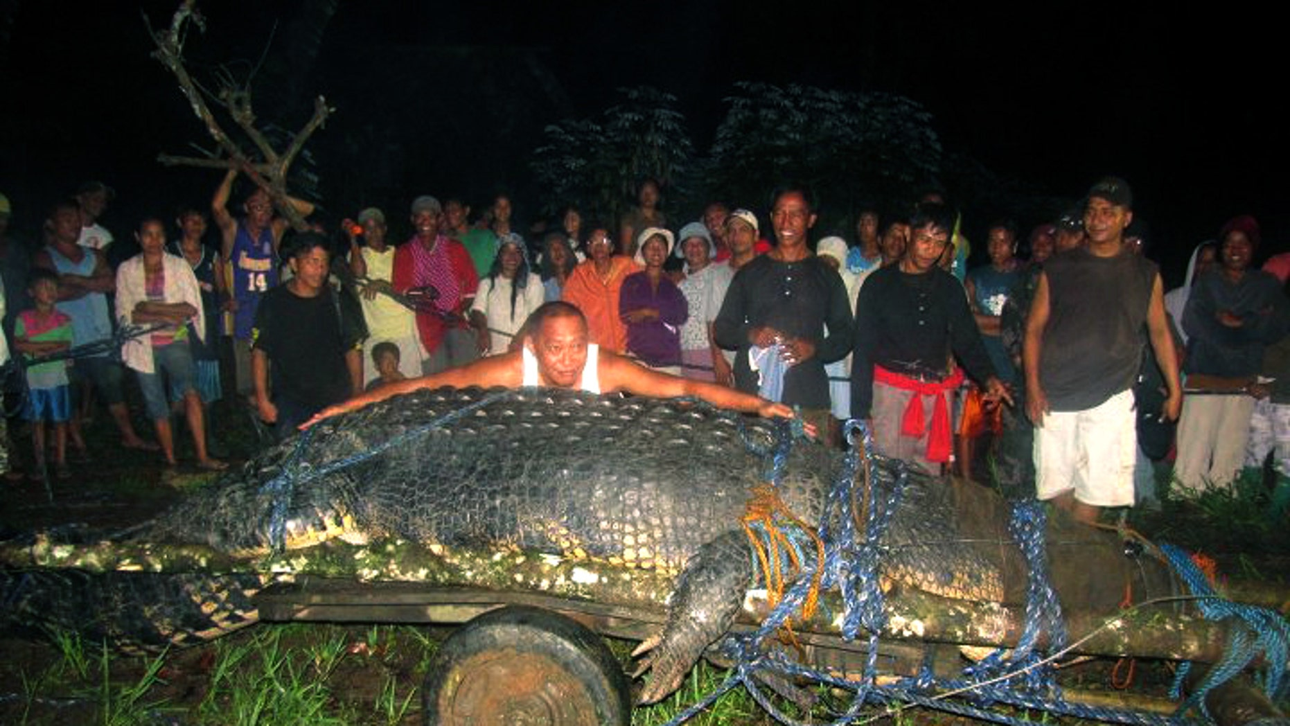 """Sept. 4, 2011 FILE photo, residents of Bunawan, southern Philippines with a huge crocodile, named """"Lolong""""  measuring 20.24 feet."""