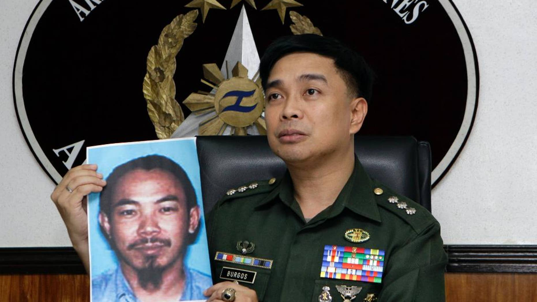 FILE - In this Feb. 2, 2012 file photo, then Armed Forces of the Philippines spokesman Col. Marcelo Burgos shows a picture of Malaysian Zulkifli bin Hir, also known as Marwan, during a press conference in suburban Quezon City, north of Manila, Philippines. Southeast Asia's top terrorist suspect hasevaded capture and survived several military assaults in the southern Philippines, where police now await DNA results to confirm if he is theman killed in the Jan. 25, 2015 raid that also left 44 police commandos dead.  (AP Photo/Pat Roque, File)