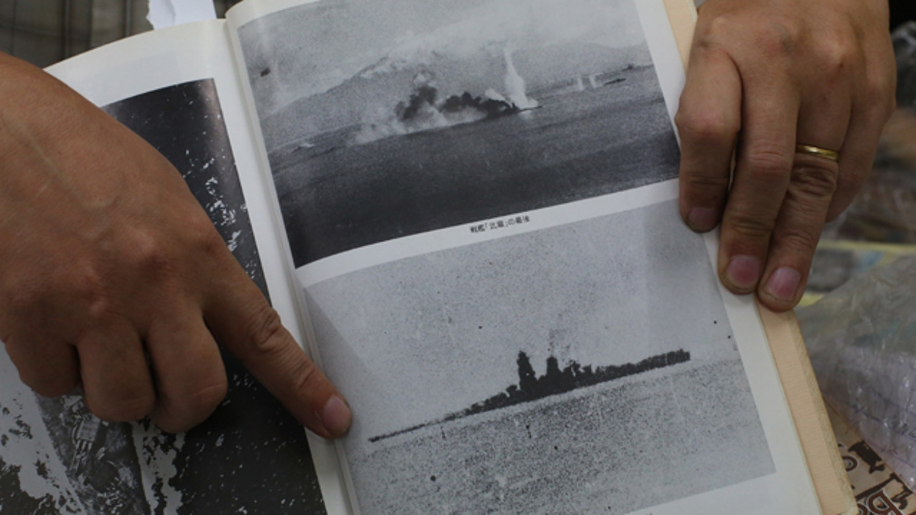 March 5, 2015: Filipino World War II historian Professor Rico Jose shows pictures before the Japanese World War II battleship Musashi sank as he talks to reporters at his office in suburban Quezon city, north of Manila. (AP Photo/Aaron Favila)
