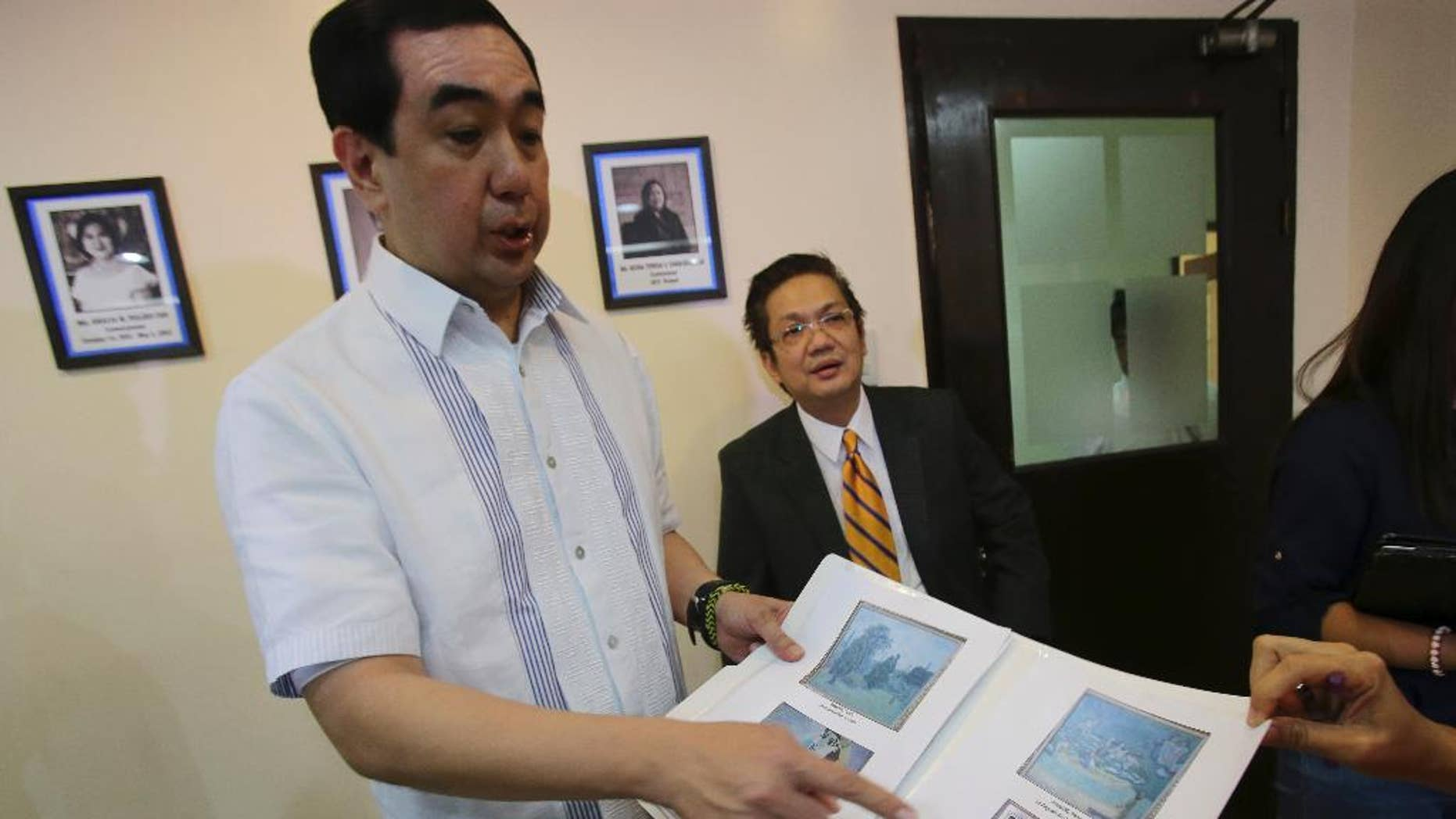 Andres Bautista, head of the Presidential Commission on Good Government, shows reporters some of the rare paintings of European masters that are allegedly part of the collection of the late dictator Ferdinand Marcos as he meets the press in suburban Mandaluyong city, east of Manila, Philippines on Wednesday, Oct. 1, 2014. Bautista says the Philippine government has seized at least 15 paintings from the former home of the Marcos, part of efforts to recover 156 artworks included in his alleged ill-gotten wealth. (AP Photo/Aaron Favila)