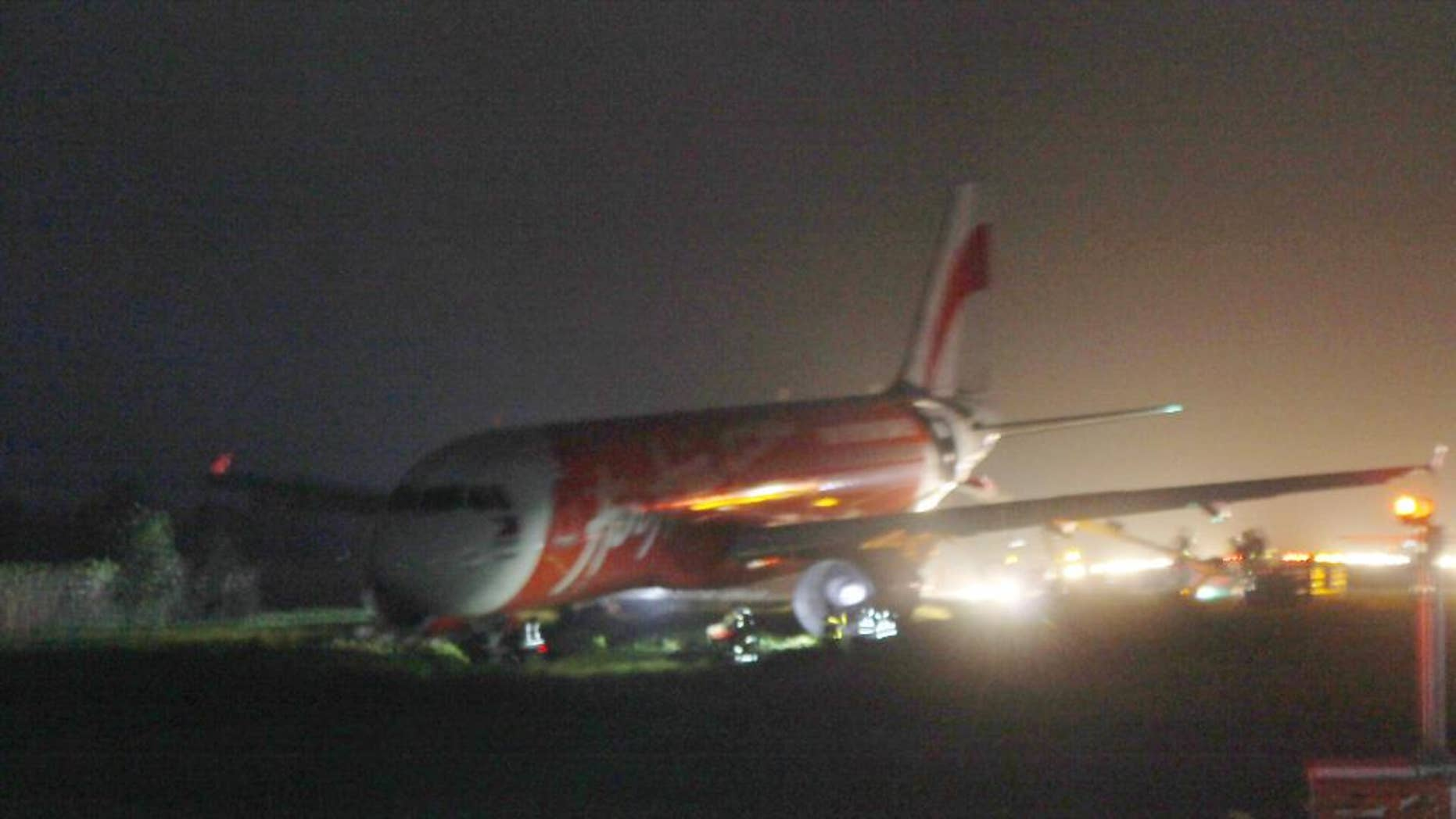 An AirAsia passenger plane sits on the grassy portion of the runway after overshooting upon landing in windy weather at Kalibo airport in Kalibo township, Aklan province in central Philippines Tuesday, Dec. 30, 2014. Giovanni Hontomin, who is in charge of AirAsia Zest's operations, told The Associated Press crewmembers activated an emergency slide to help passengers disembark safely from the Airbus aircraft. There were no immediate reports of injuries to the passengers and crew and the plane remained stuck on a grassy area near the runway's end. (AP Photo/Jun Aguirre)