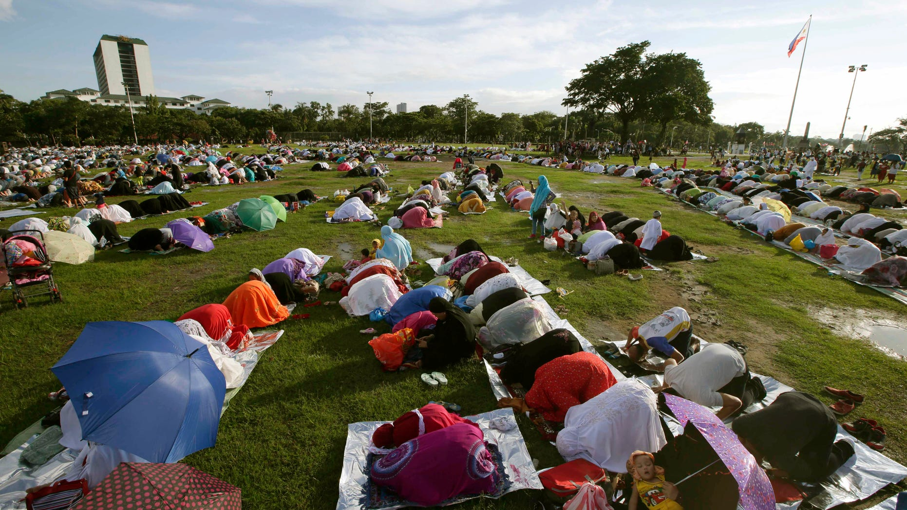 July 28, 2014 - Filipino Muslims gather at Manila's Rizal Park to pray in celebration of Eid al-Fitr marking the end of the holy month of Ramadan, in Manila, Philippines. Abu Sayyaf gunmen killed at least 21 villagers, including women and children, traveling to visit relatives and celebrate the end of Ramadan, military officials said.