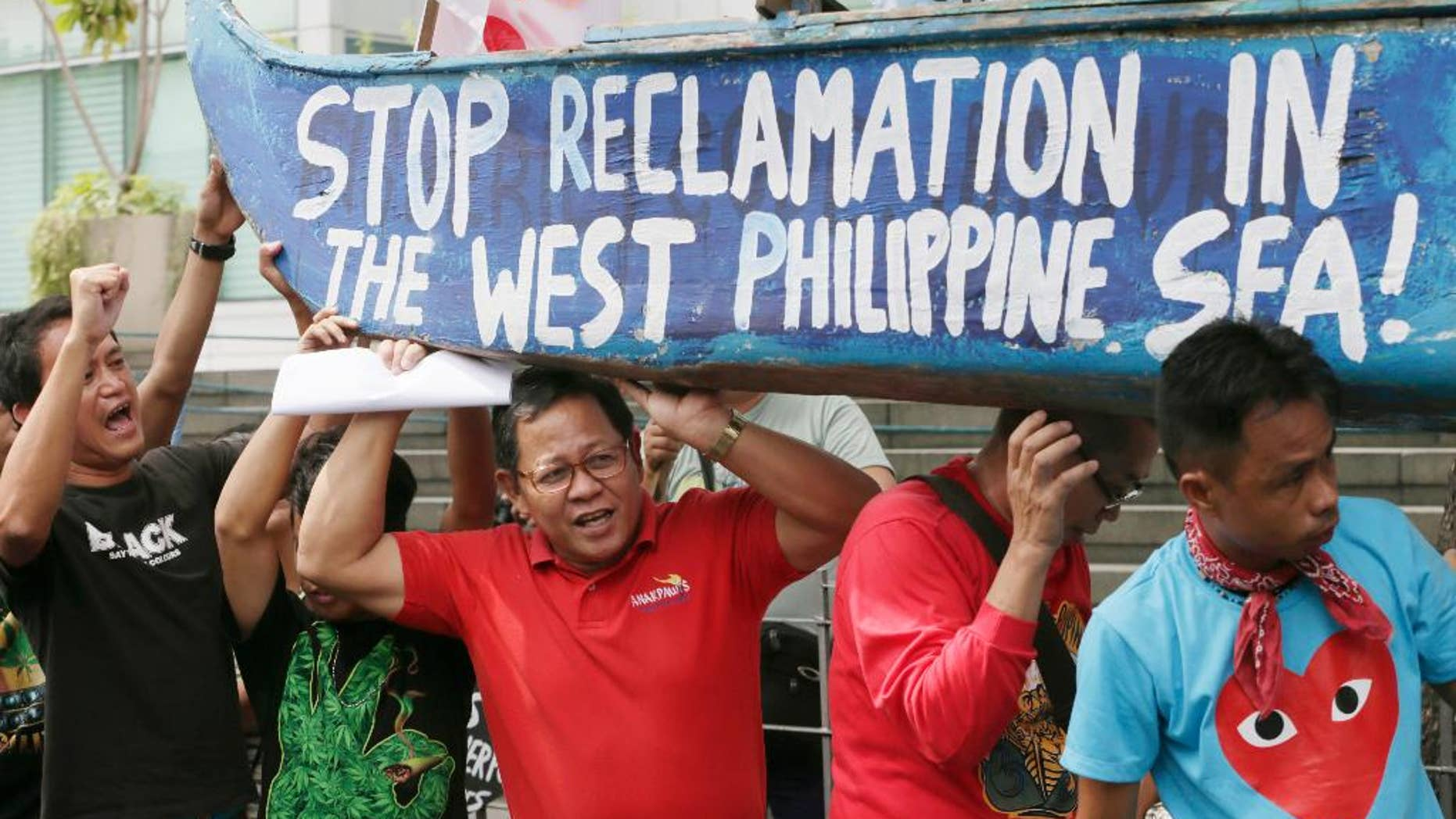In this July 3, 2015, file photo, protesters carry a boat painted with slogans during a rally outside the Chinese Consulate at the financial district of Makati city, east of Manila, Philippines, to protest China's reclamations of disputed islands off South China Sea. China is standing pat on its decision to reject arbitration by an international tribunal that will begin formal hearings this week to resolve a long-seething feud with the Philippines over the South China Sea, Beijing's ambassador to Manila said Monday, July 6, 2015. (AP Photo/Bullit Marquez)