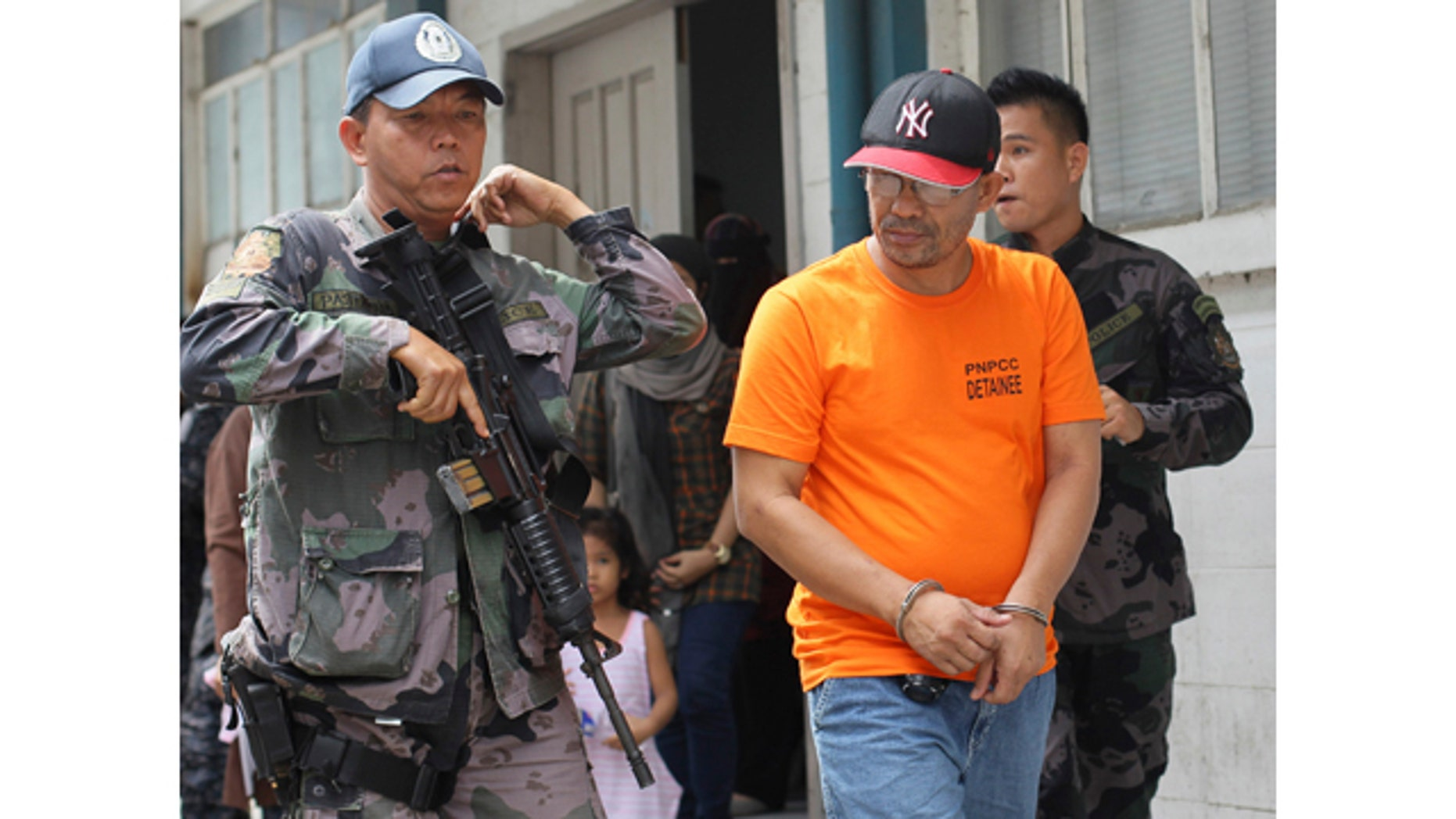 June 20, 2014: A Philippine police officer escorts Abu Sayyaf extremist group leader Khair Mundos, right, after his arraignment at courts inside a police camp in Taguig City, south of Manila, Philippines.  The captured Abu Sayyaf commander has told investigators that a top Southeast Asian terror suspect, who the military reported was killed in a U.S.-backed airstrike two years ago, is alive and being harbored by a hardline Muslim rebel group in the southern Philippines, a confidential police report said. (AP Photo/Mark Cristino)