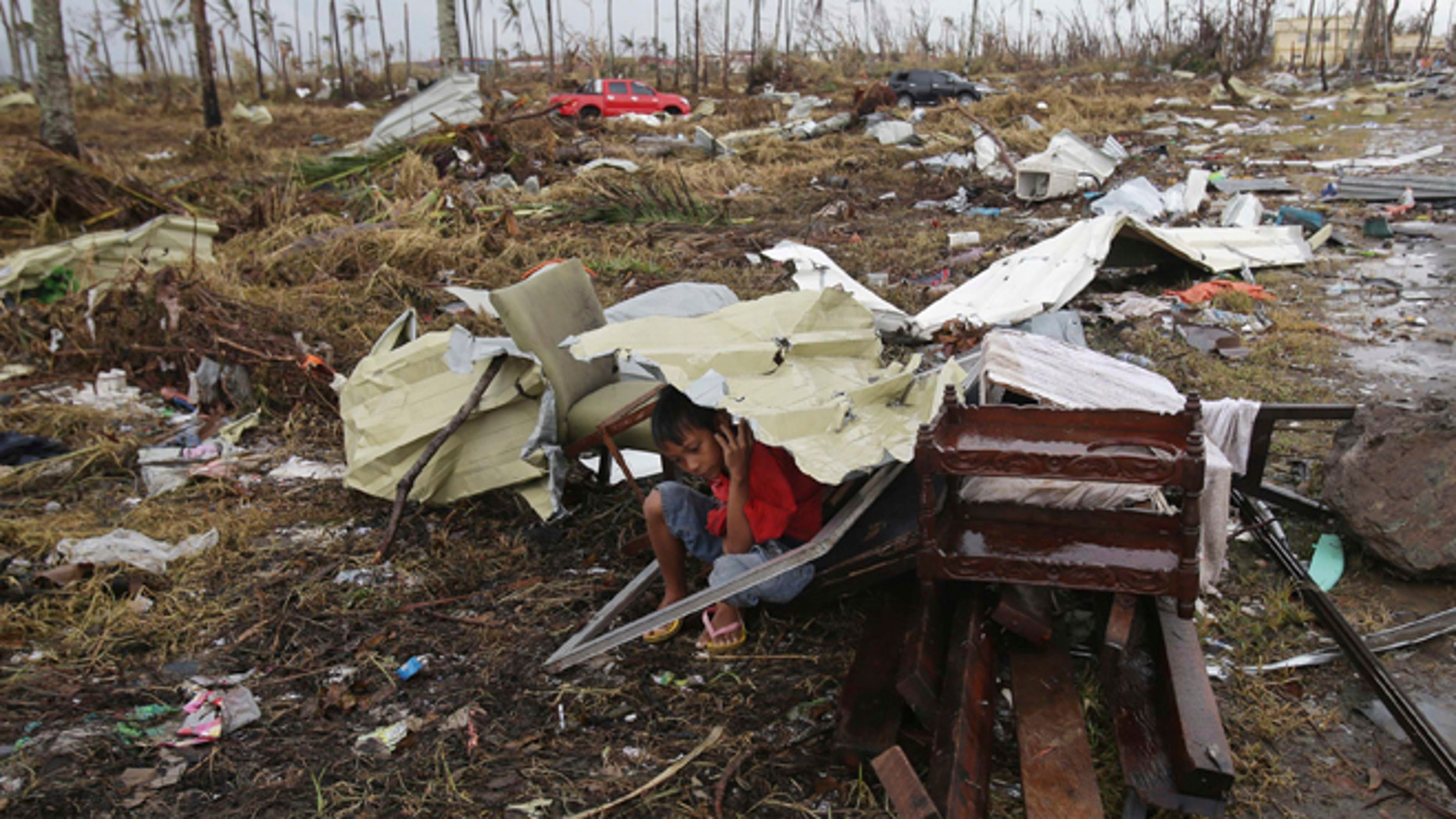 A young survivor uses the remains of some parts of a house to shield him from rain in Tacloban city, Leyte province, central Philippines on Tuesday, Nov. 12, 2013.