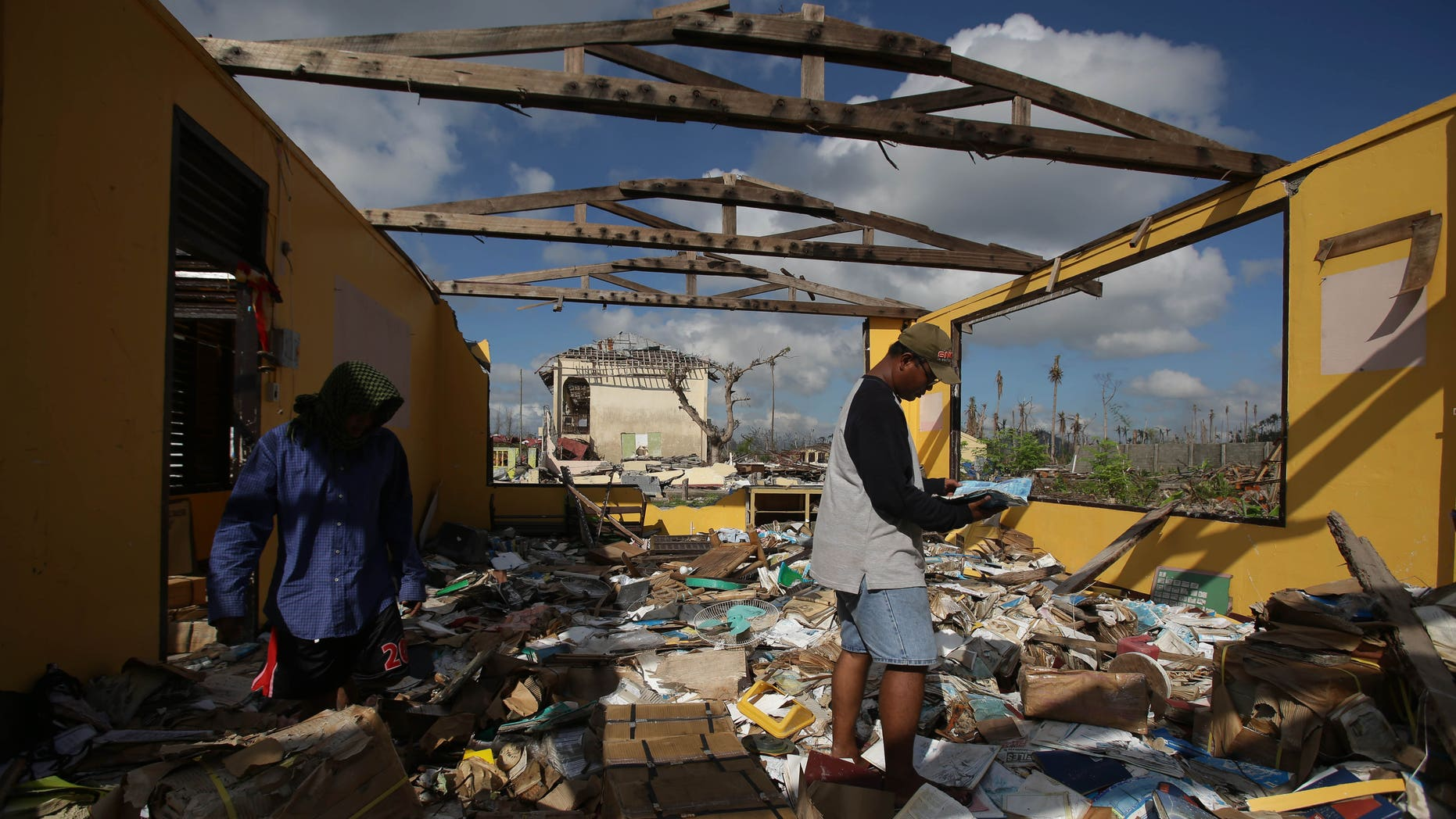 Dec. 9, 2013 - Typhoon survivor and district property custodian Norman Acala examines a book as he tries to save pieces from the school library at the Daniel Z. Romualdez Memorial Elementary School at typhoon-ravaged Tolosa town, Leyte province, central Philippines. Tens of thousands are living amid the ruins of their former lives, underneath shelters made from scavenged materials and handouts.