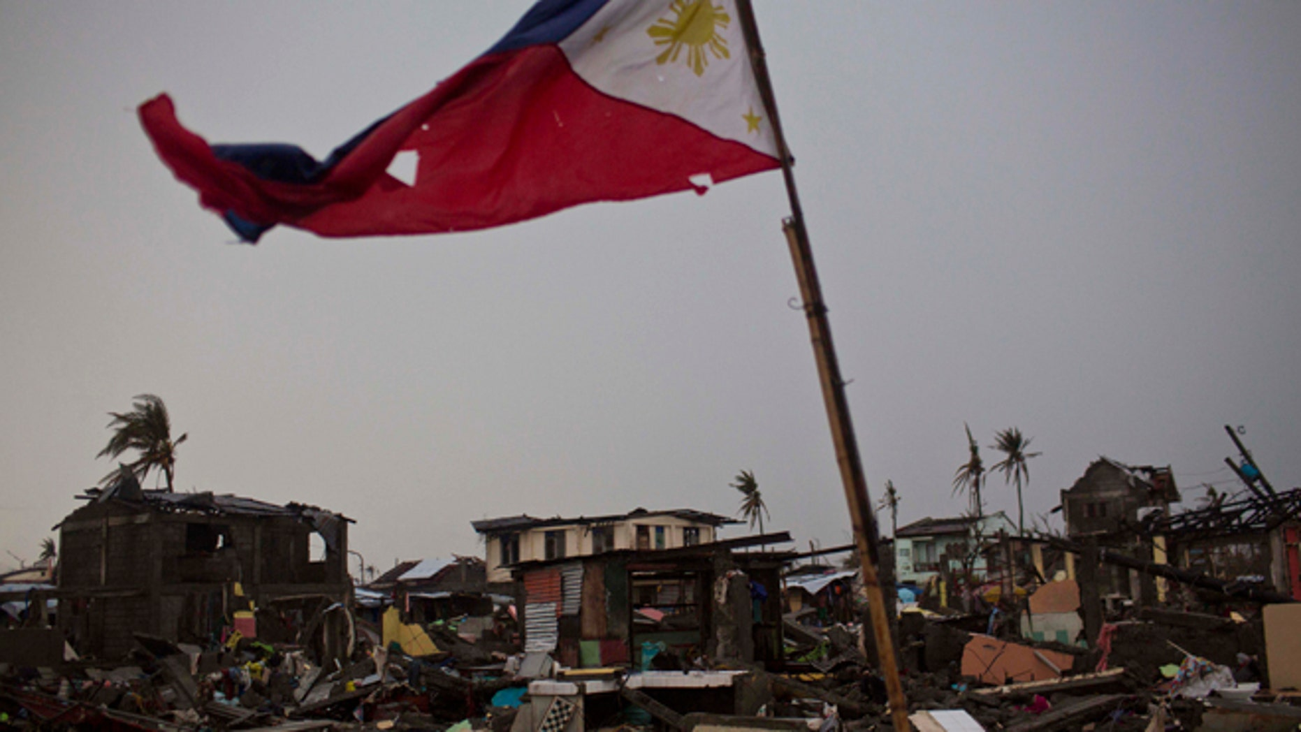 A flag of the Philippines flies over a destroyed neighborhood in Tacloban, Philippines on Friday Nov. 22, 2013. Hundreds of thousands of people were displaced by Typhoon Haiyan, which tore across several islands in the eastern Philippines on Nov. 8. (AP Photo/David Guttenfelder)