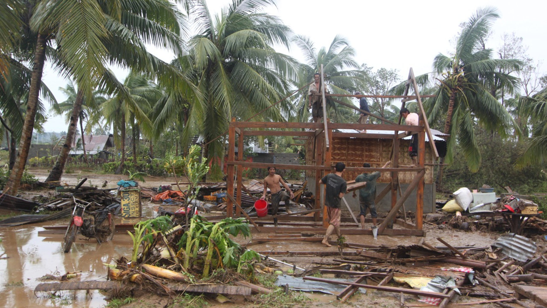 Dec. 4, 2012: Residents repair their damaged homes after Typhoon Bopha made landfall in Compostela Valley in southeastern Philippines.