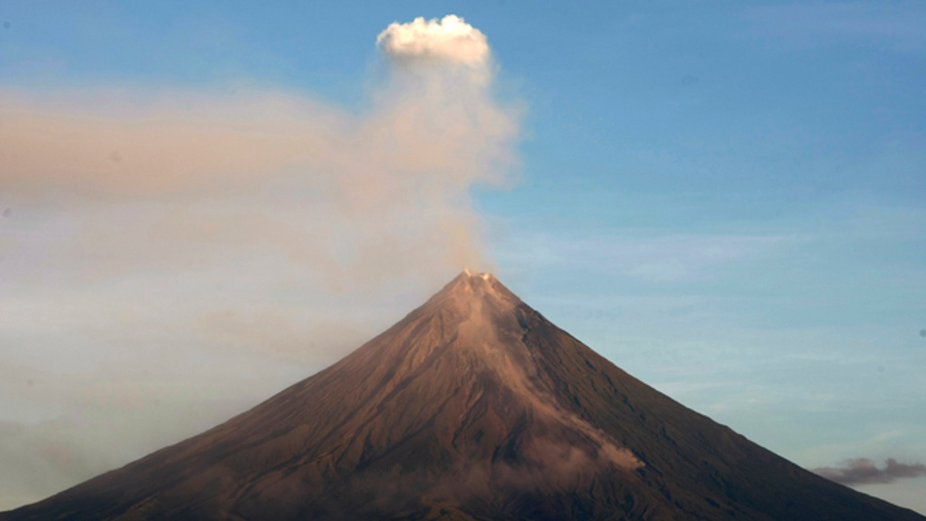 "Mayon volcano spews ash anew in another ""ash explosion"" as viewed in Legazpi city, Albay province, about 500 kilometers south of Manila. Security forces will forcibly evacuate thousands of residents reluctant to leave their farms around the slopes of the country's most active volcano despite fears of a major eruption."