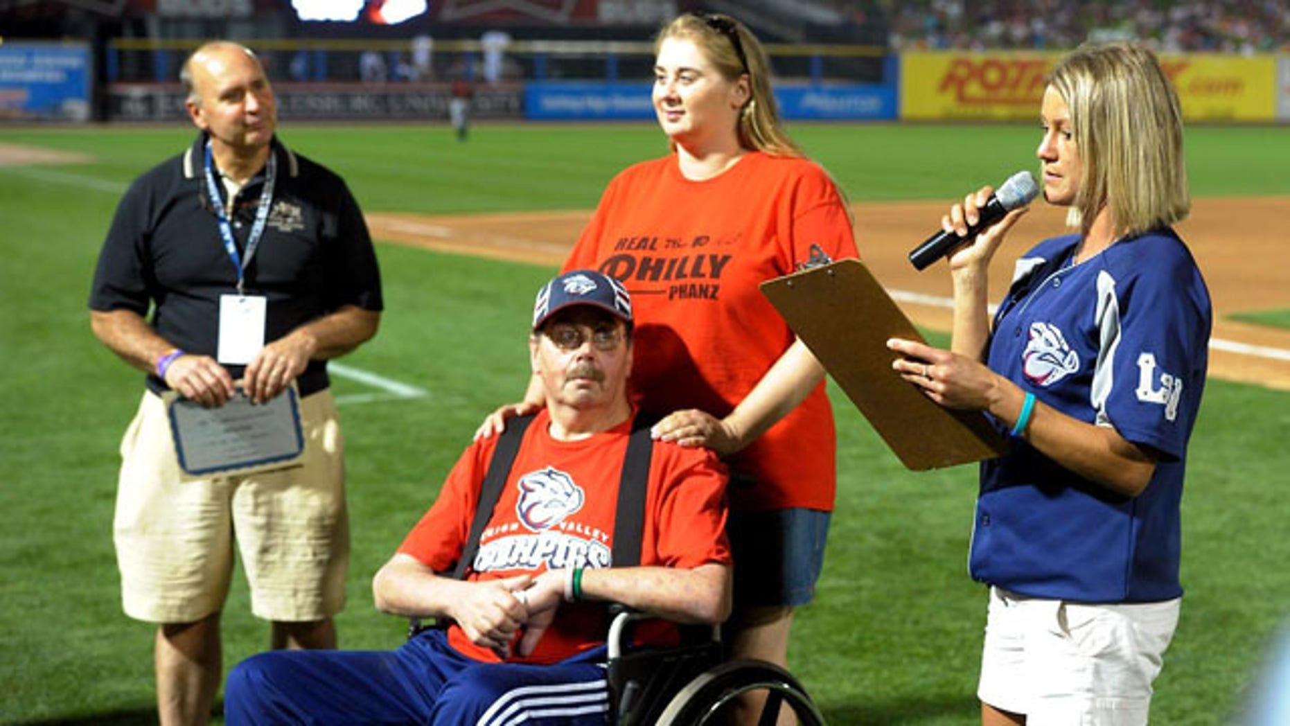 August 20, 2013: Kevin Reichel, left, of Reichel Funeral Home, watches along with Steve Paul, of Freemansburg Pa., and his daughter Robyn Paul as Lindsey Knupp, right, director of promotions and entertainment for the Lehigh Valley Iron Pigs minor league baseball team, reads the winning essay written by Steve Paul during the middile of the sixth inning at Coca-Cola Park, in Allentown, Pa. (AP Photo)