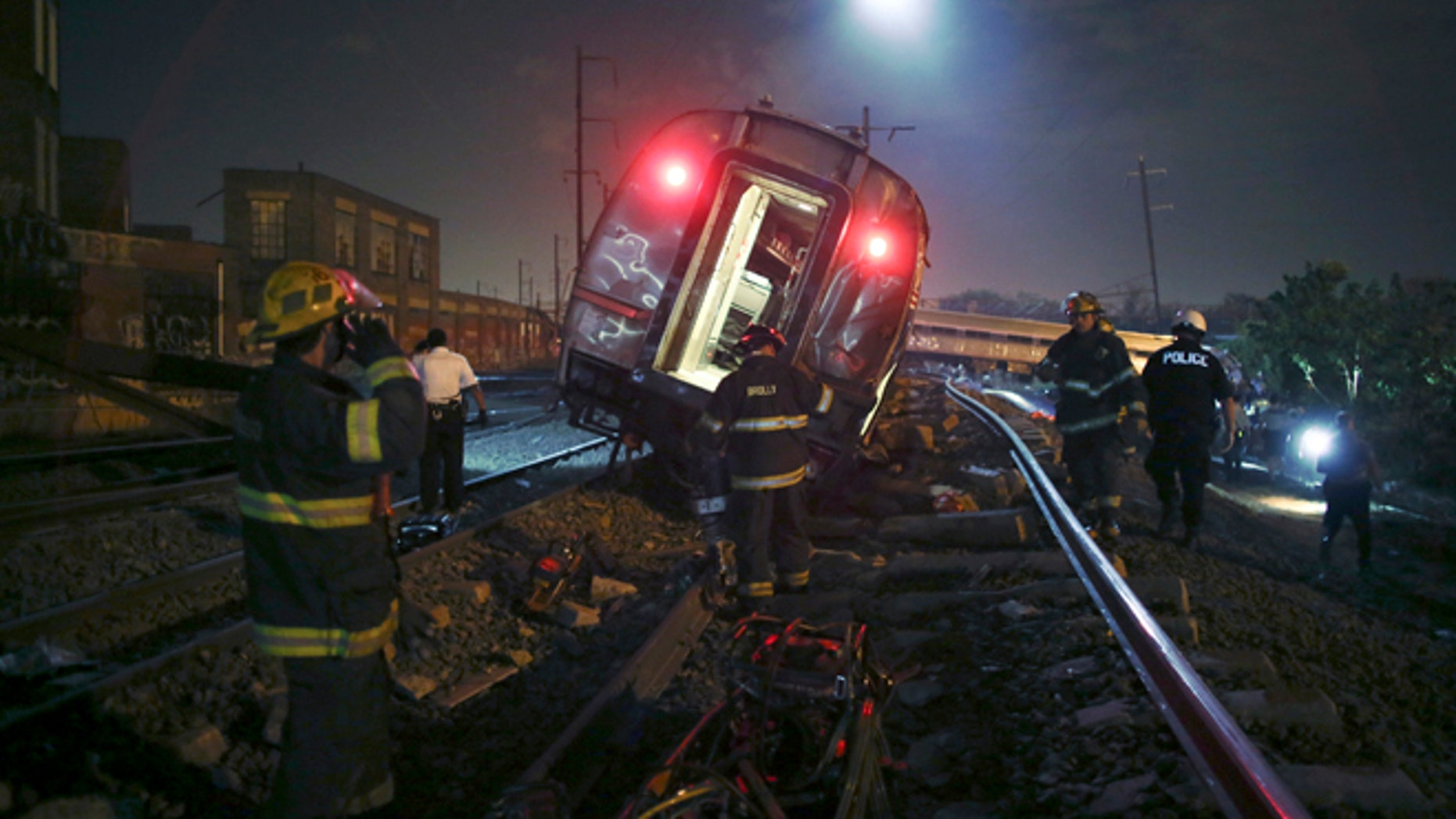 Emergency personnel work the scene of a deadly train wreck, Tuesday, May 12, 2015, in Philadelphia. An Amtrak train headed to New York City derailed and tipped over in Philadelphia. (AP Photo/ Joseph Kaczmarek)