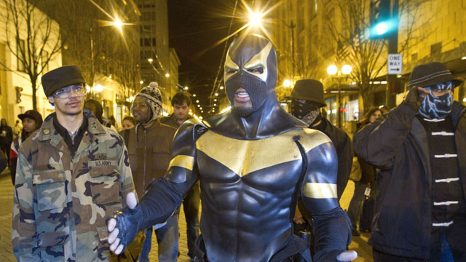 In this photo taken Feb. 26, 2011, Self-described superhero Phoenix Jones meets protestors at Westlake Park in Seattle.