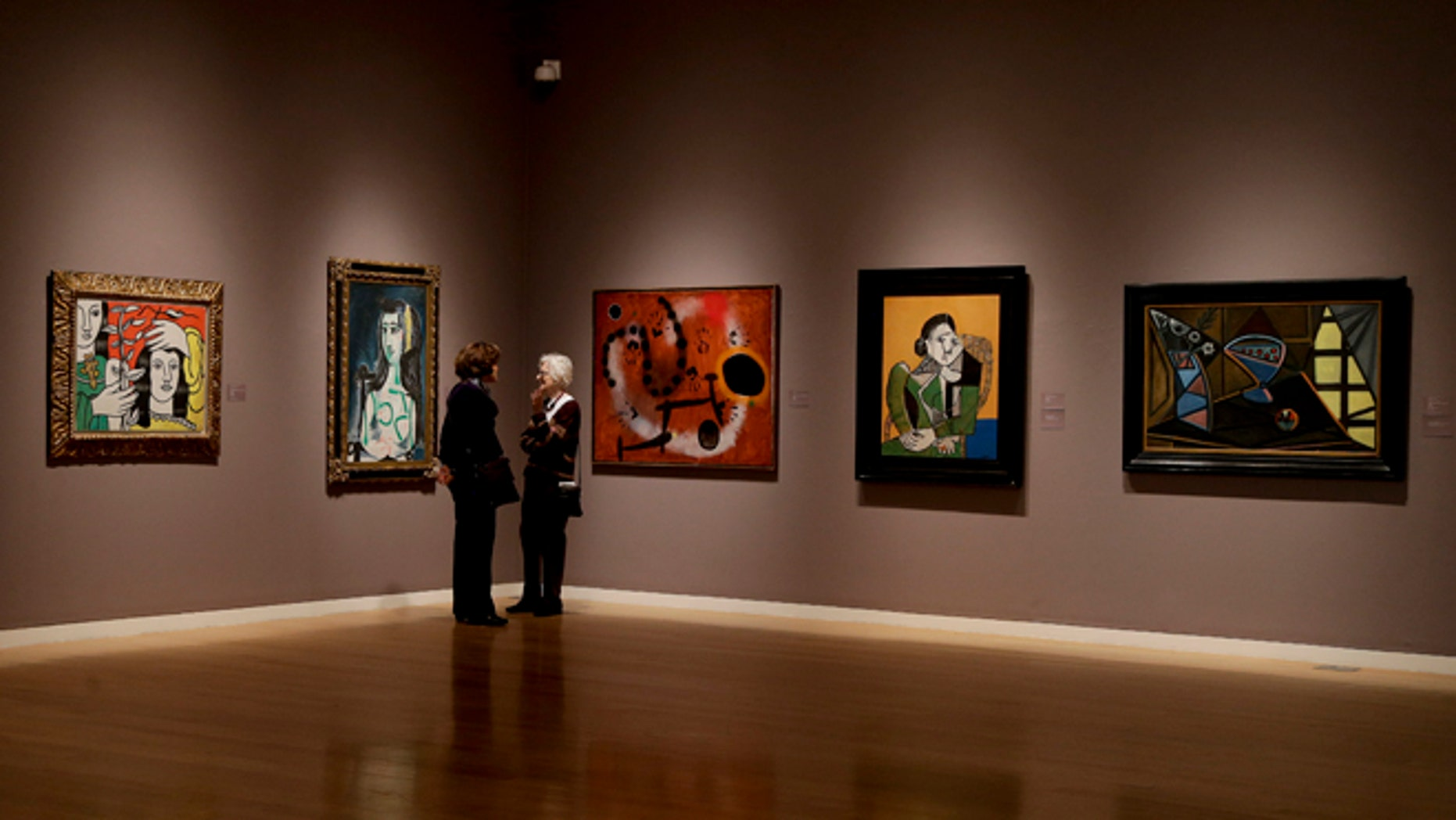 Prospective buyers talk amongst paintings by Pablo Picasso, Joan Miro and Fernand Leger during a preview exhibition for Sotheby's Spring Evening Sale of impressionistic and modern art, Friday, May 2, 2014, in New York. The sale will begin on May 7. (AP Photo/Julie Jacobson)