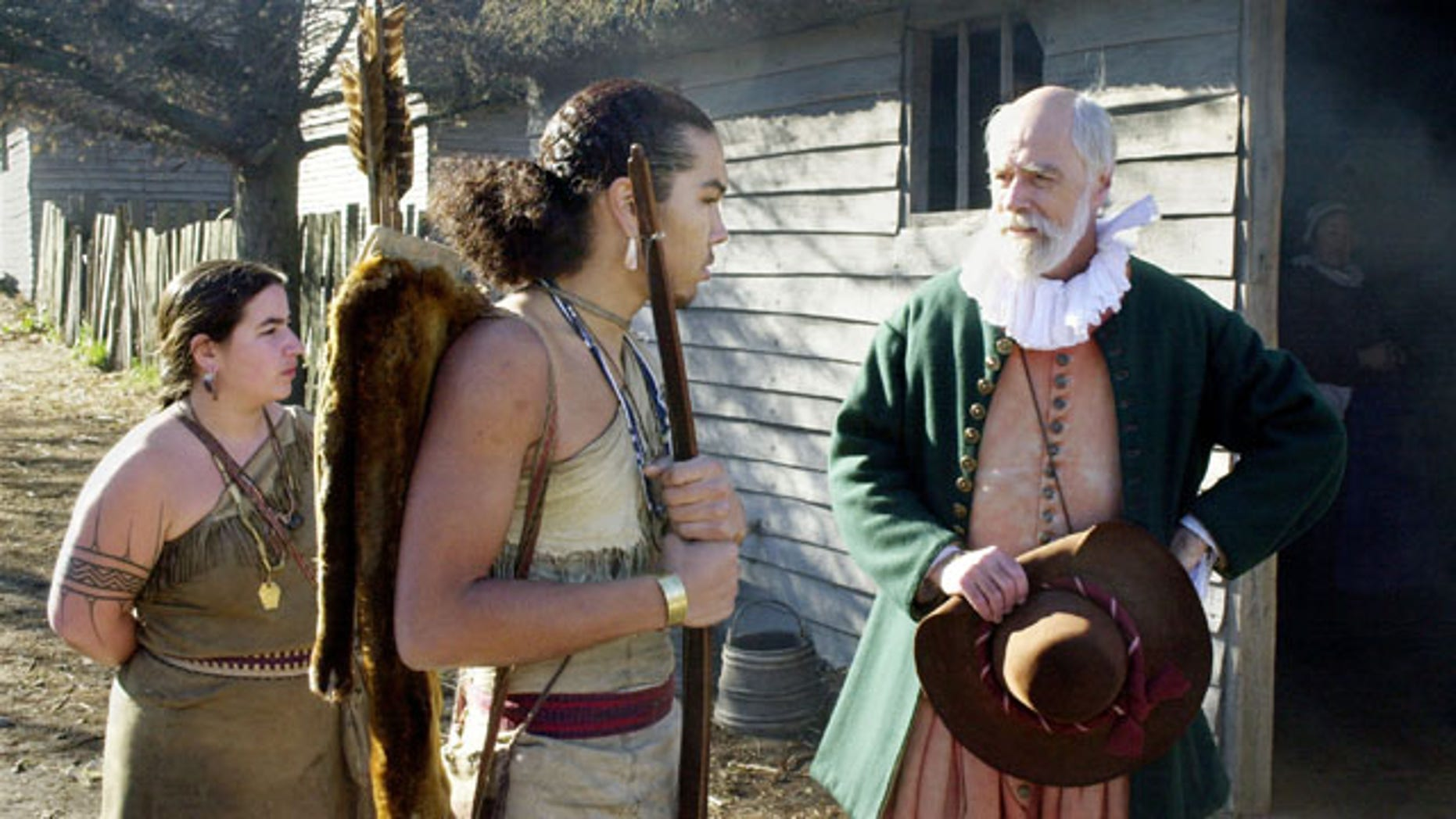 PLYMOUTH, MA - NOVEMBER 25:  John Kemp (R) portrays pilgrim Steven Hopkins meeting with the colonists Wampanoag Indian interpreter Hobbamock, played by Jonathan Perry (C), as another Wampanoag, played by Melanie Roderick (L), looks on November 25, 2003 at Plimoth Plantation in Plymouth, Massachusetts. In real life, parents have the difficult job of teaching their children about the truth about what led to the holiday. (Photo by Michael Springer/Getty Images)