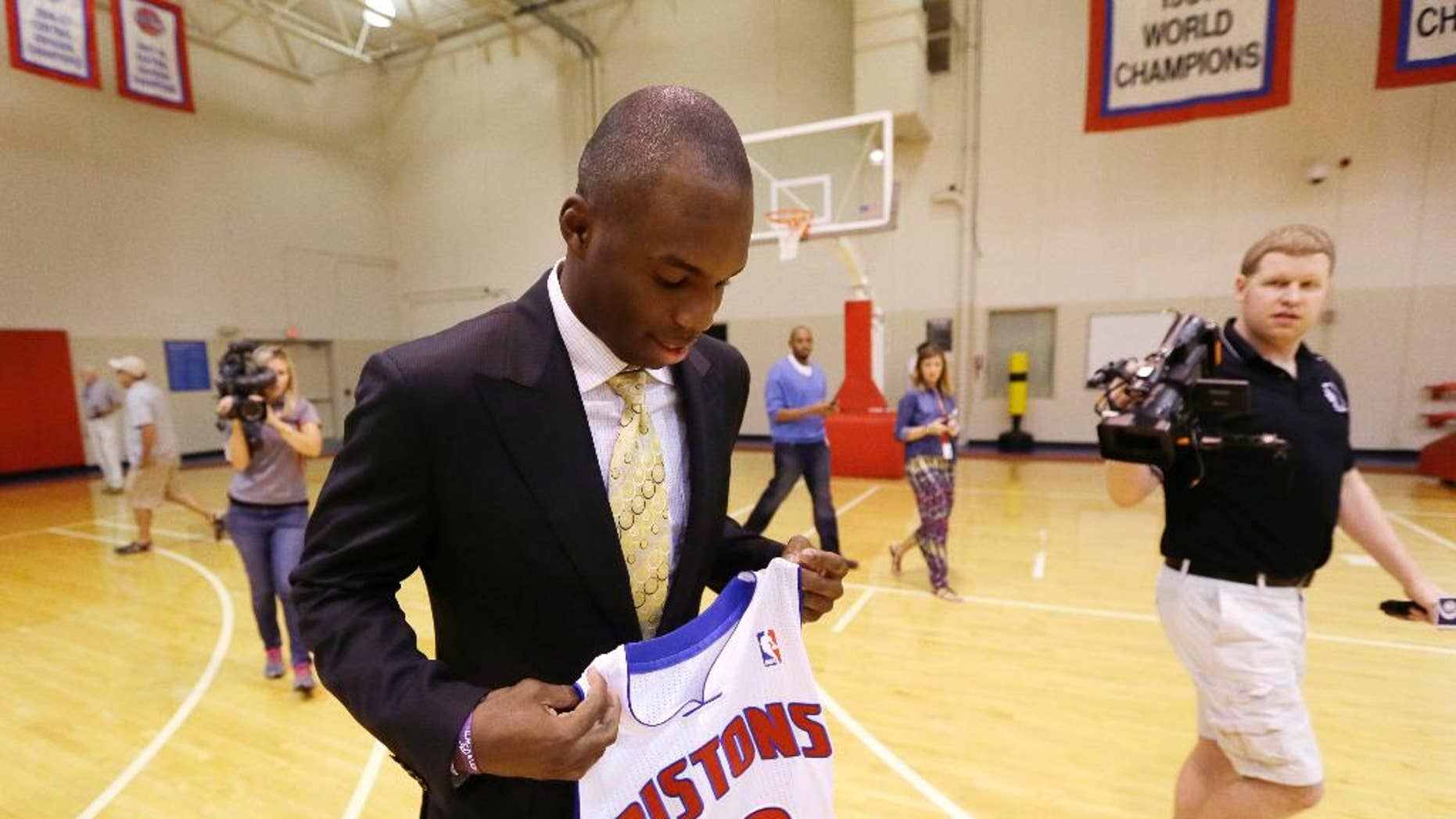 Detroit Pistons guard Jodie Meeks is followed by the media as he holds his new jersey at the team's practice facility in Auburn Hills, Mich., Monday, July 14, 2014. The Pistons hope he can provide some much-needed perimeter shooting this season under new coach Stan Van Gundy. (AP Photo/Carlos Osorio)