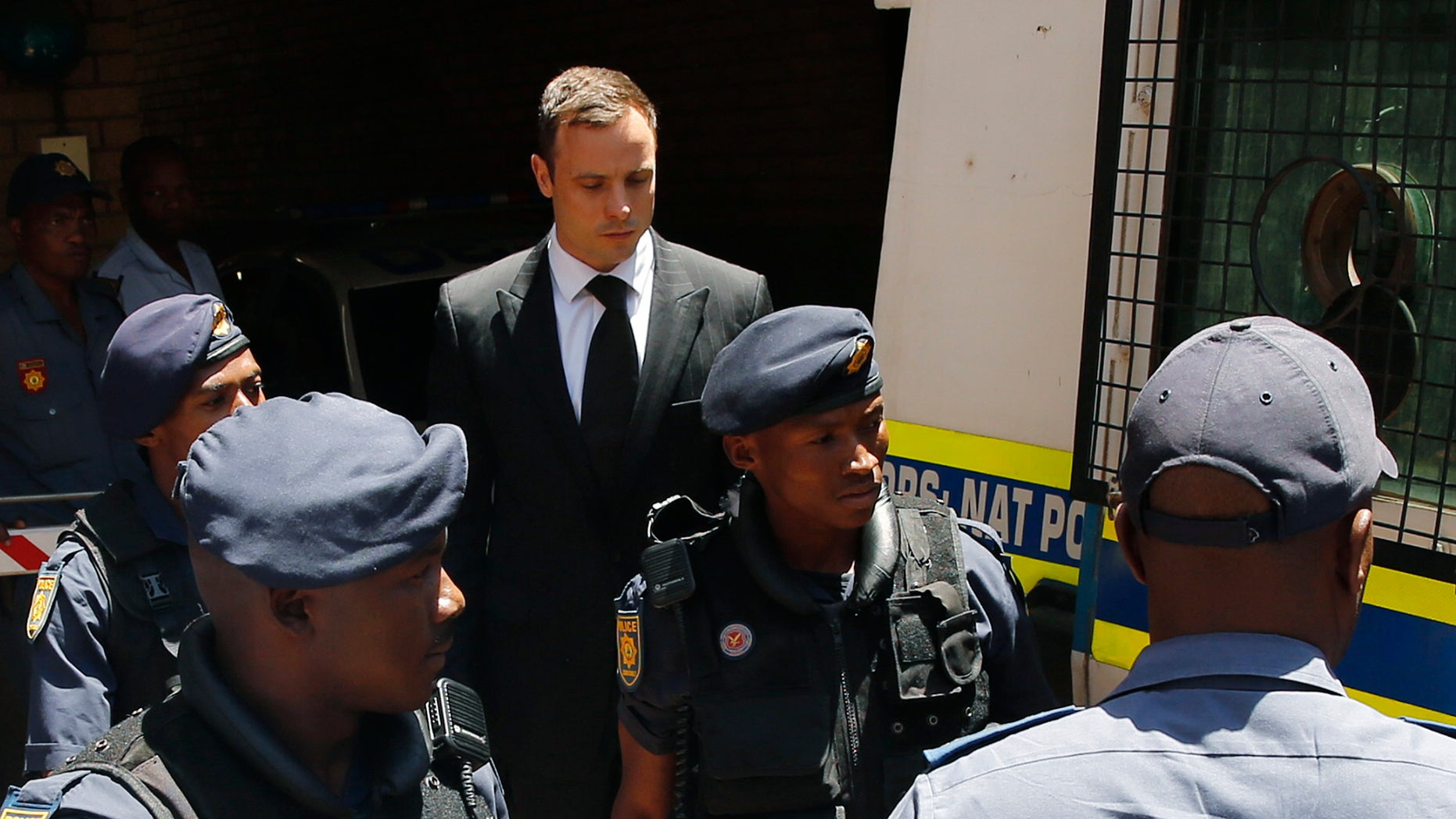 October 21, 2014 - South African Olympic and Paralympic sprinter Oscar Pistorius is escorted to a police van after his sentencing in Pretoria.