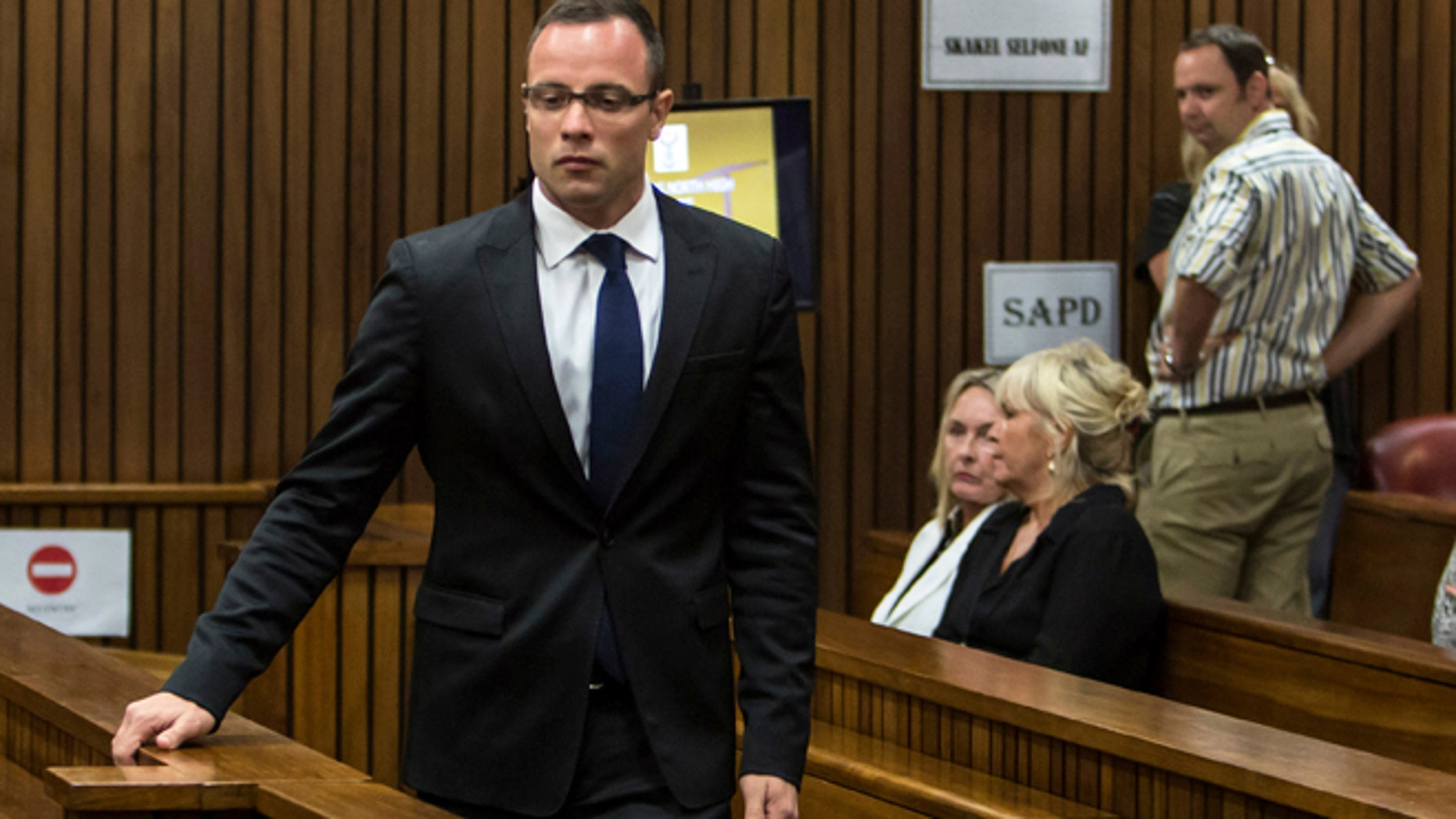 March 17, 2014: Oscar Pistorius, left, walks past June Steenkamp, back left, mother of Reeva Steenkamp, and Jenny Strydom, as he arrives in court in Pretoria, South Africa.