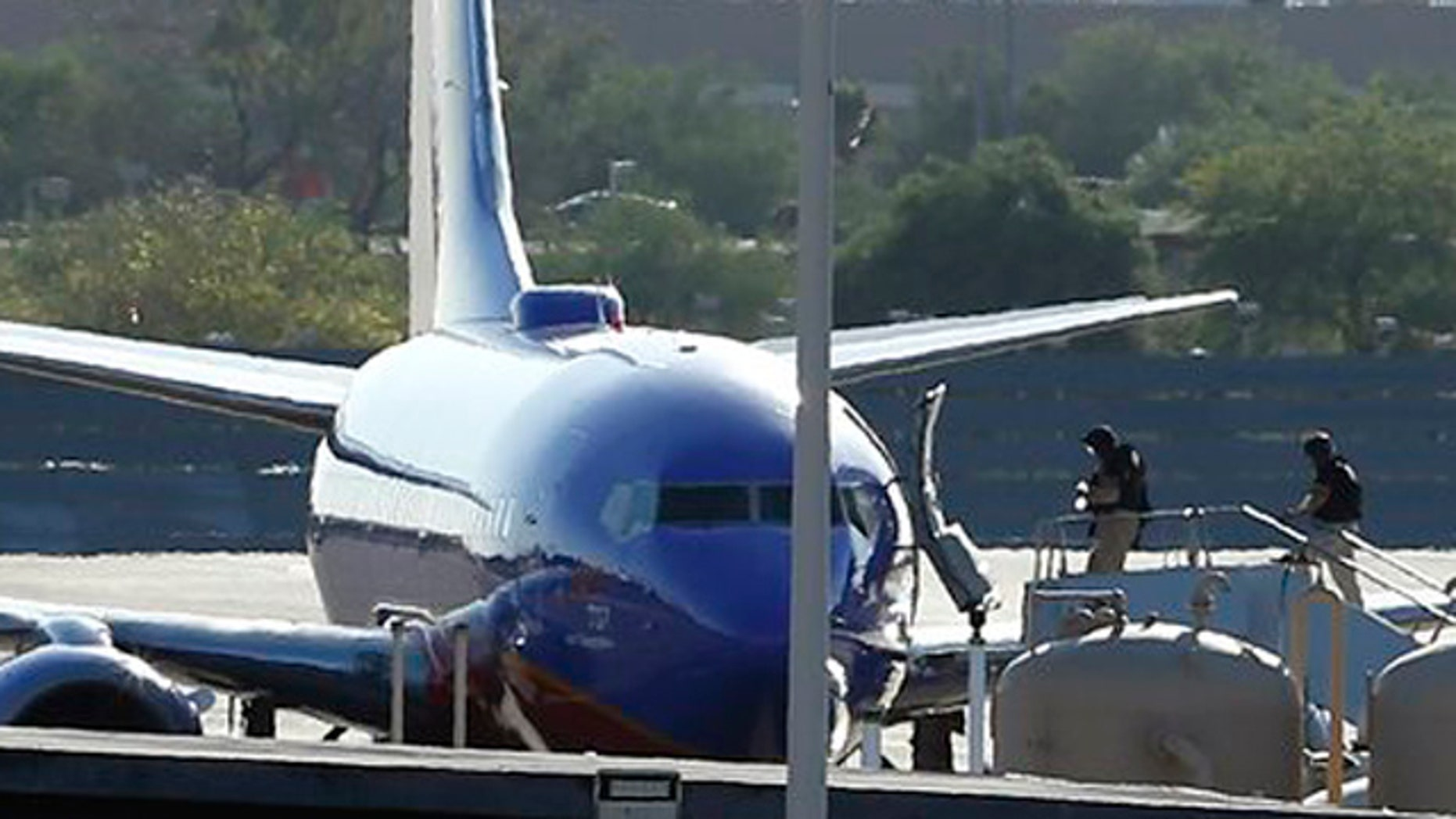 "June 10, 2013: Members of the bomb squad walk onto a Southwest Airlines plane on the ground at Phoenix Sky Harbor International Airport after the FBI says a ""telephonic bomb threat"" against a Southwest flight from Los Angeles to Texas led to the plane being diverted to Phoenix."