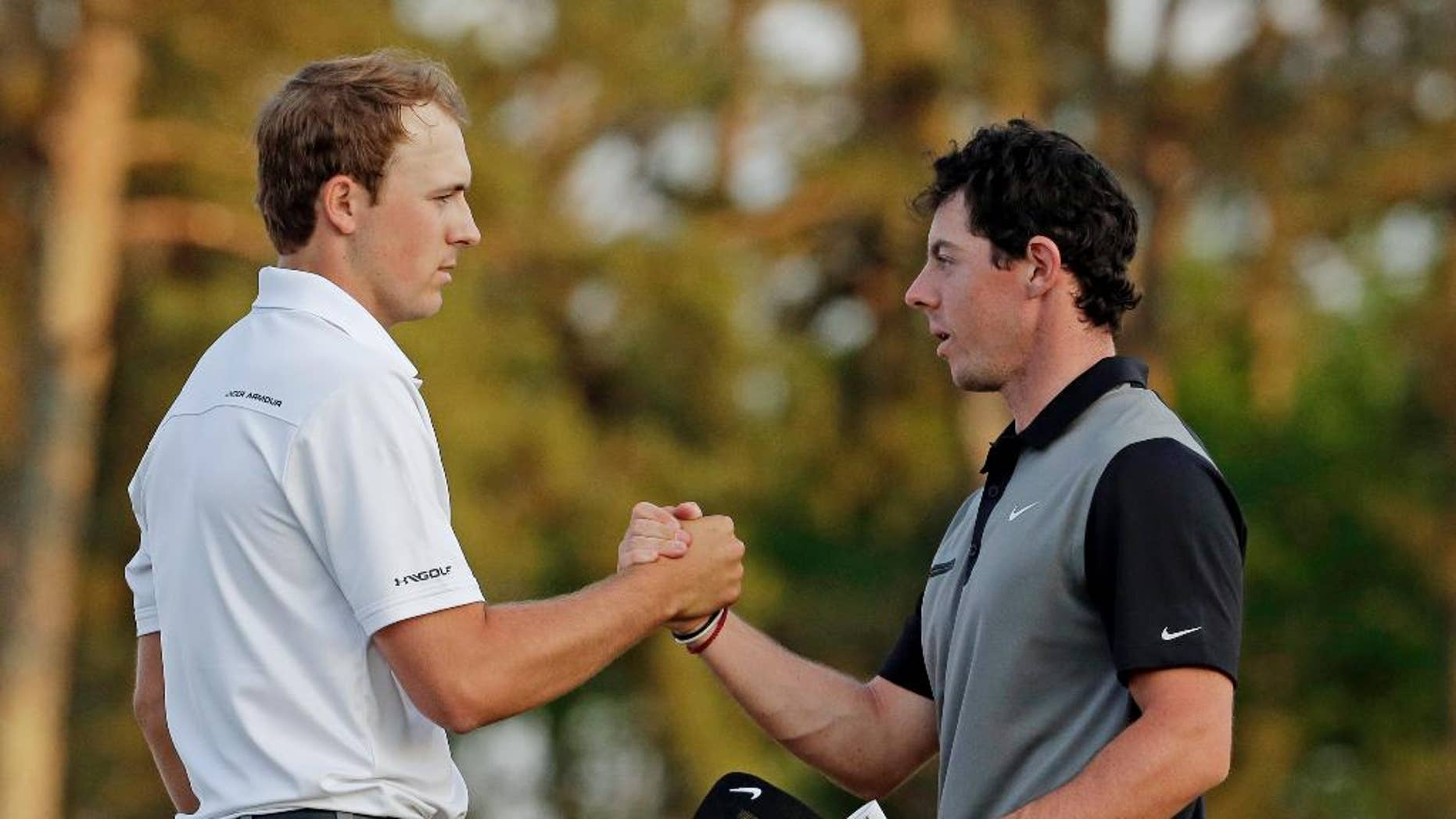 FILE - In this April 11, 2014, file photo, Jordan Spieth, left, shakes hands with Rory McIlroy, of Northern Ireland, on the 18th green following the second round of the Masters golf tournament in Augusta, Ga. The match that didn't happen in San Francisco will be available in stroke play at The Players Championship this week. Match Play winner Rory McIlroy, ranked No. 1, and Masters champion Jordan Spieth, ranked No. 2, are in the same group for the opening two rounds.(AP Photo/Charlie Riedel, File)