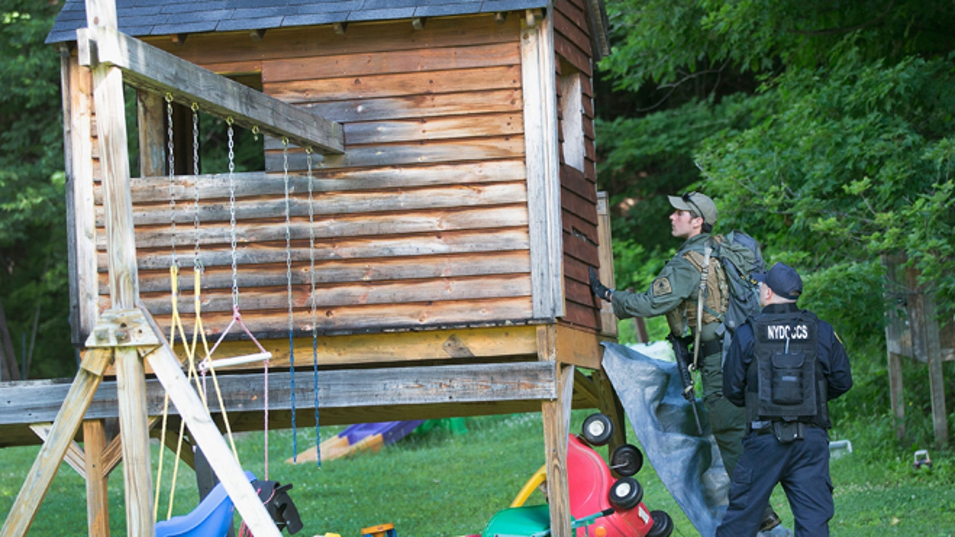 Law enforcement personnel search a child's playhouse as the manhunt for convicted murderers, Richard Matt and David Sweat, on June 26, 2015 in Chasm Falls, New York. (Photo by Scott Olson/Getty Images)