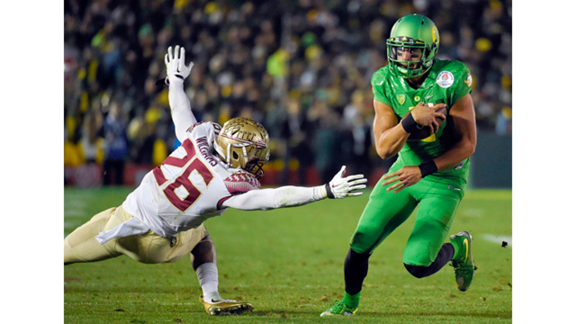 Jan. 1, 2015: Oregon quarterback Marcus Mariota, right, scores past Florida State defensive back P.J. Williams during the second half of the Rose Bowl NCAA college football playoff semifinal in Pasadena, Calif. (AP Photo/Mark J. Terrill)