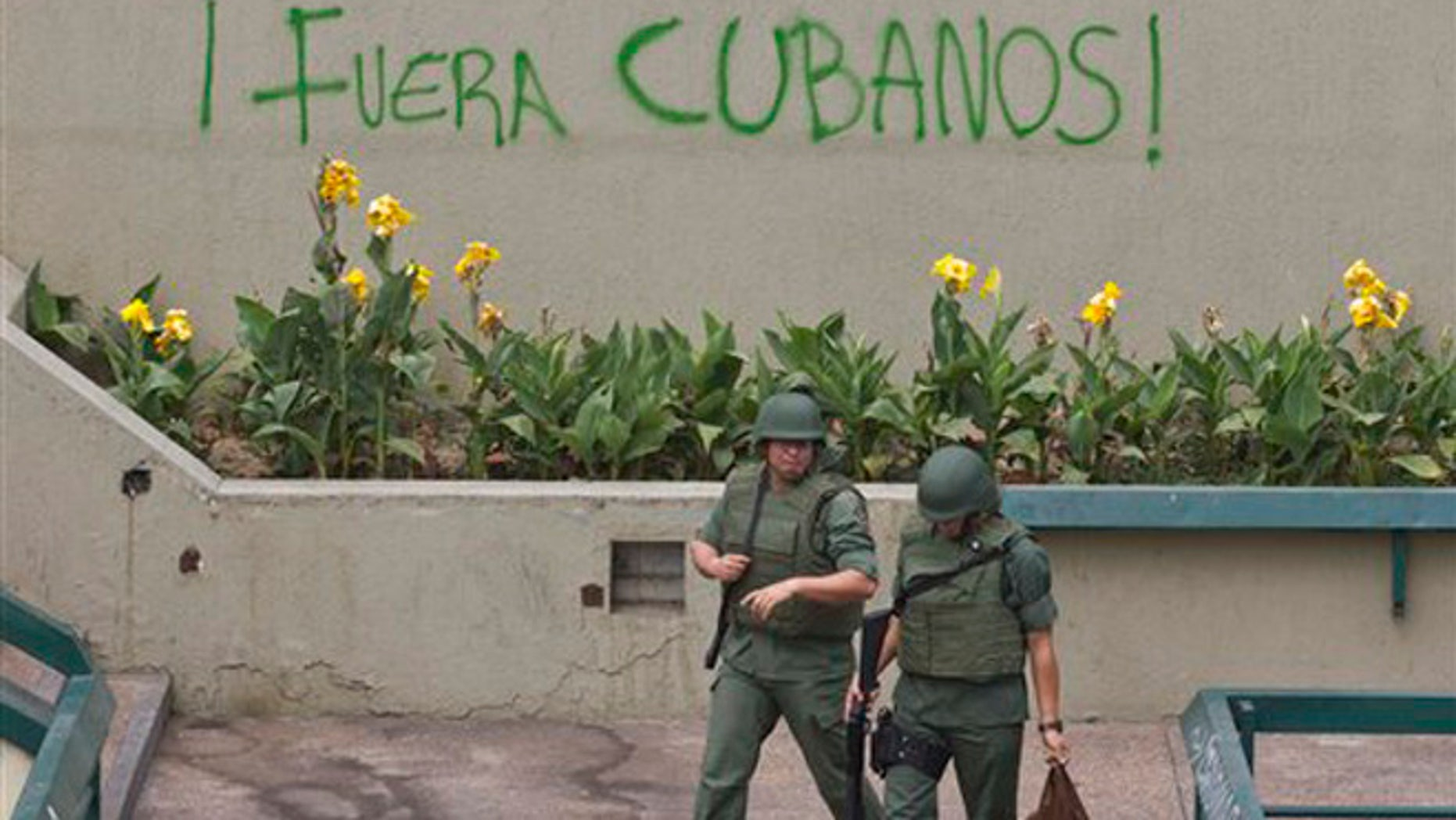 """Bolivarian National Guard officers patrol Plaza Altamira after taking control of it, in Caracas, Venezuela, Monday, March 17, 2014. Government security forces took control of a Caracas plaza and surrounding neighborhoods Monday morning that had become the center of student-led protests. The graffiti on the wall reads in Spanish """"Cubans Out!"""". Clusters of National Guardsmen were a visible presence not only on Plaza Altamira, but along the principal streets extending from it in the municipality of Chacao."""