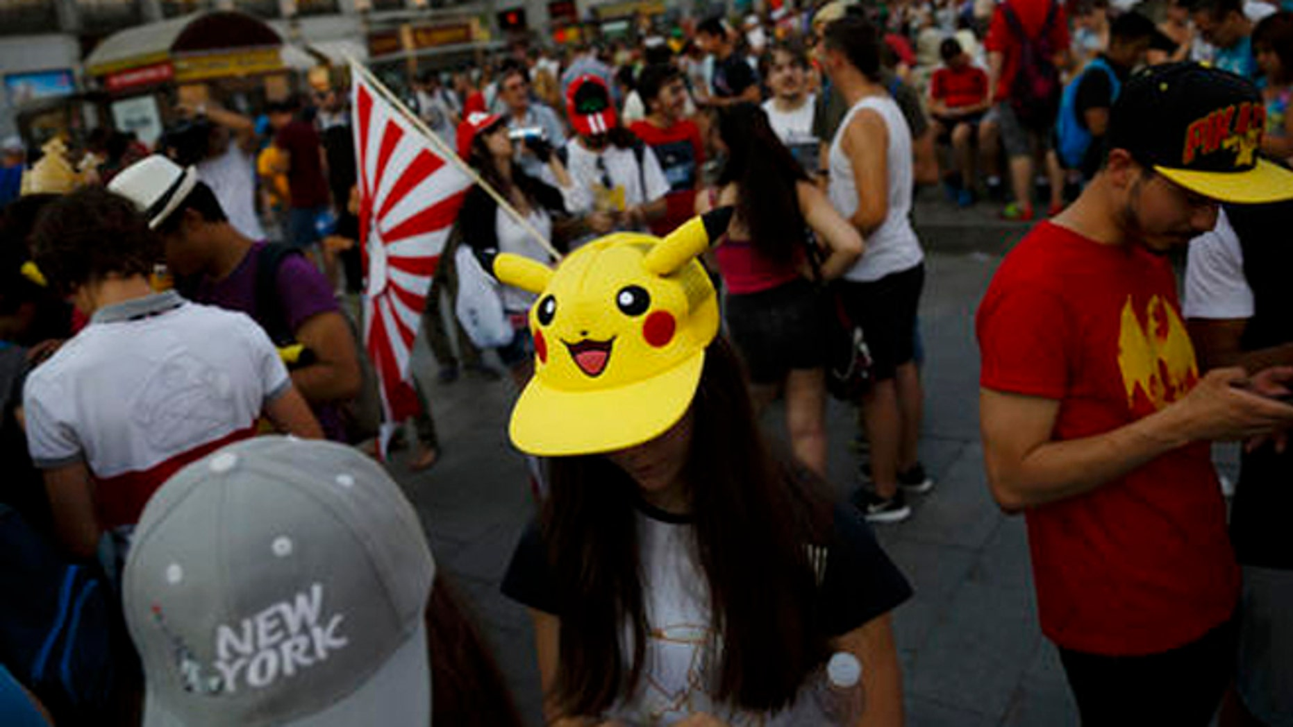 """FILE - In this Thursday, July 28, 2016, file photo, fans play the highly addictive """"Pokemon Go"""" game during a gathering in central Madrid, Spain, to play the computer game. Since debuting to wild adulation in the U.S., Australia and New Zealand this month, the game from Google spinoff Niantic Inc. has spread like wildfire, launching in more than 30 countries or territories, but not Brazil. For athletes and other visitors caught up in the wave, not having access is just one more knock against an Olympics that officials are racing to get ready. The opening ceremony takes place Friday, Aug. 5. (AP Photo/Daniel Ochoa de Olza, File)"""